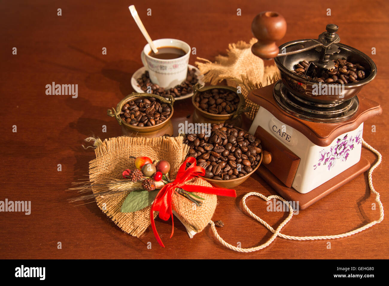 Grinder with coffee beans in copper bowls and Cup with composition of jute - Stock Image