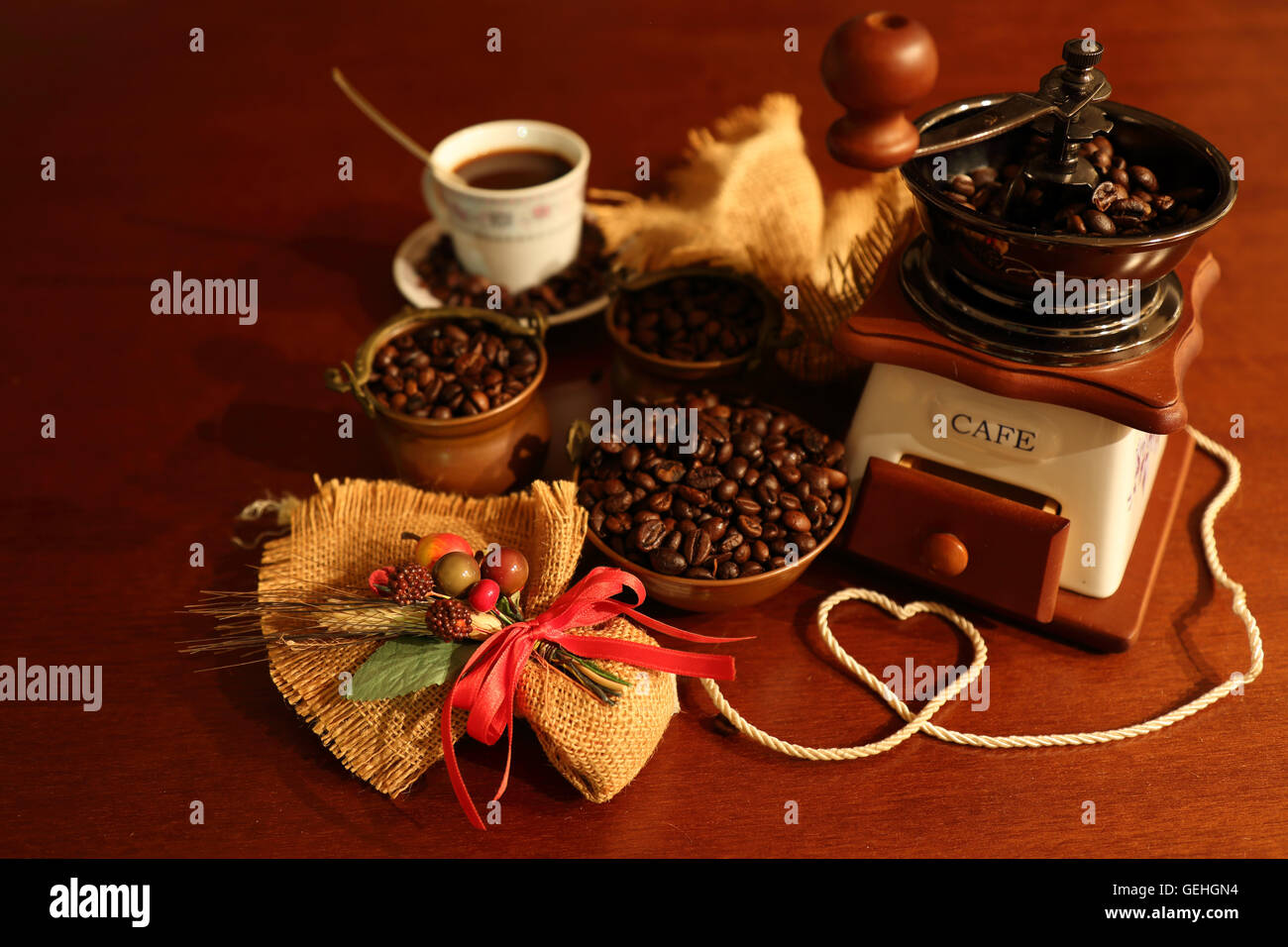 Grinder with coffee beans in copper bowls and Cup with composition of jute Stock Photo