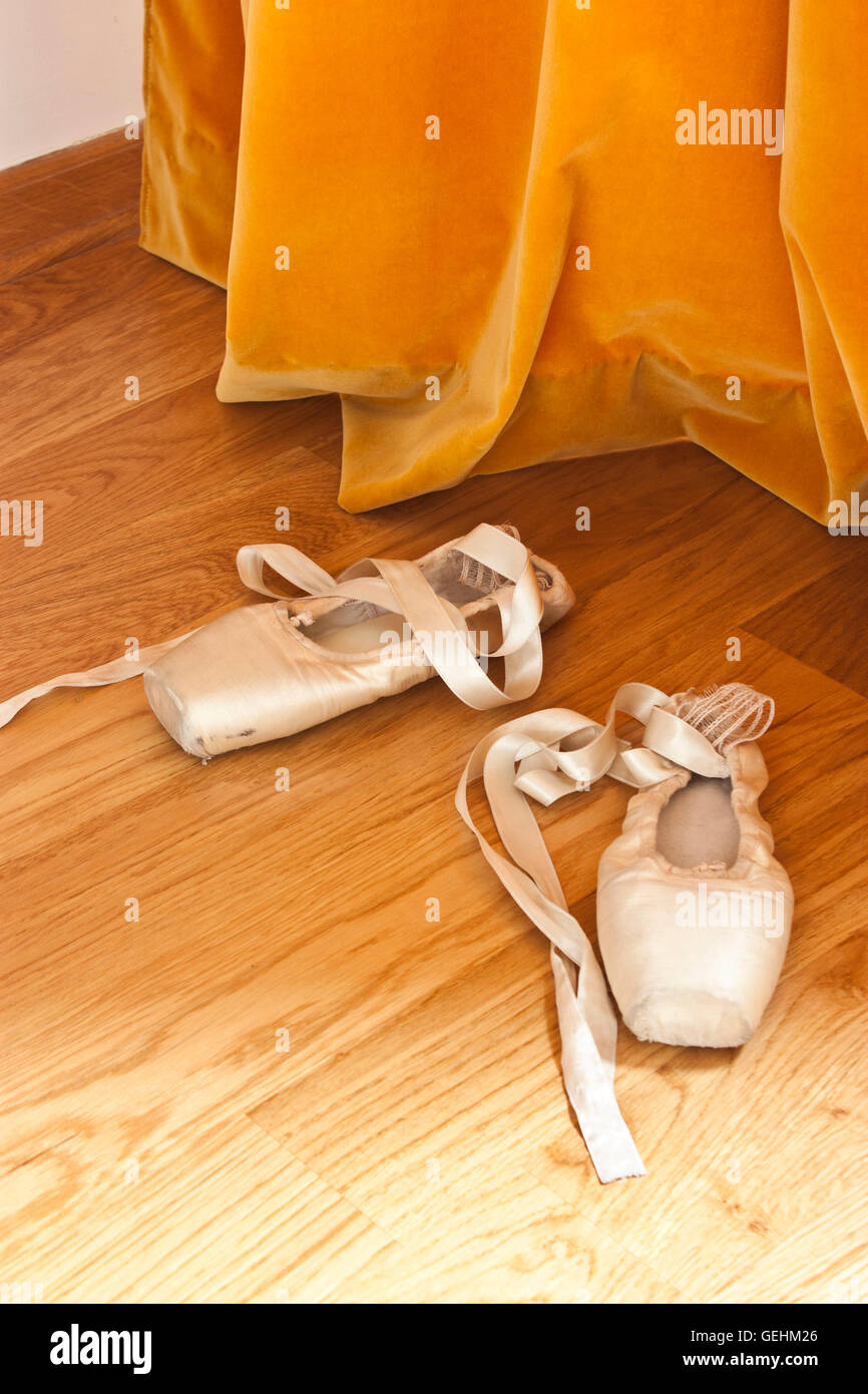 Pointe ballet shoes on the wooden floor in front of the orange curtain - Stock Image