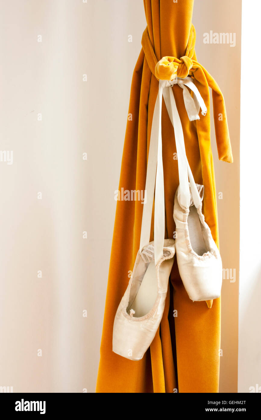 Pointe ballet shoes hanging on a theater curtain - Stock Image
