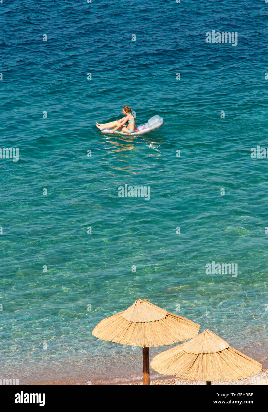 Young girl on inflatable beach mattress in the sea going away from the shore - Stock Image