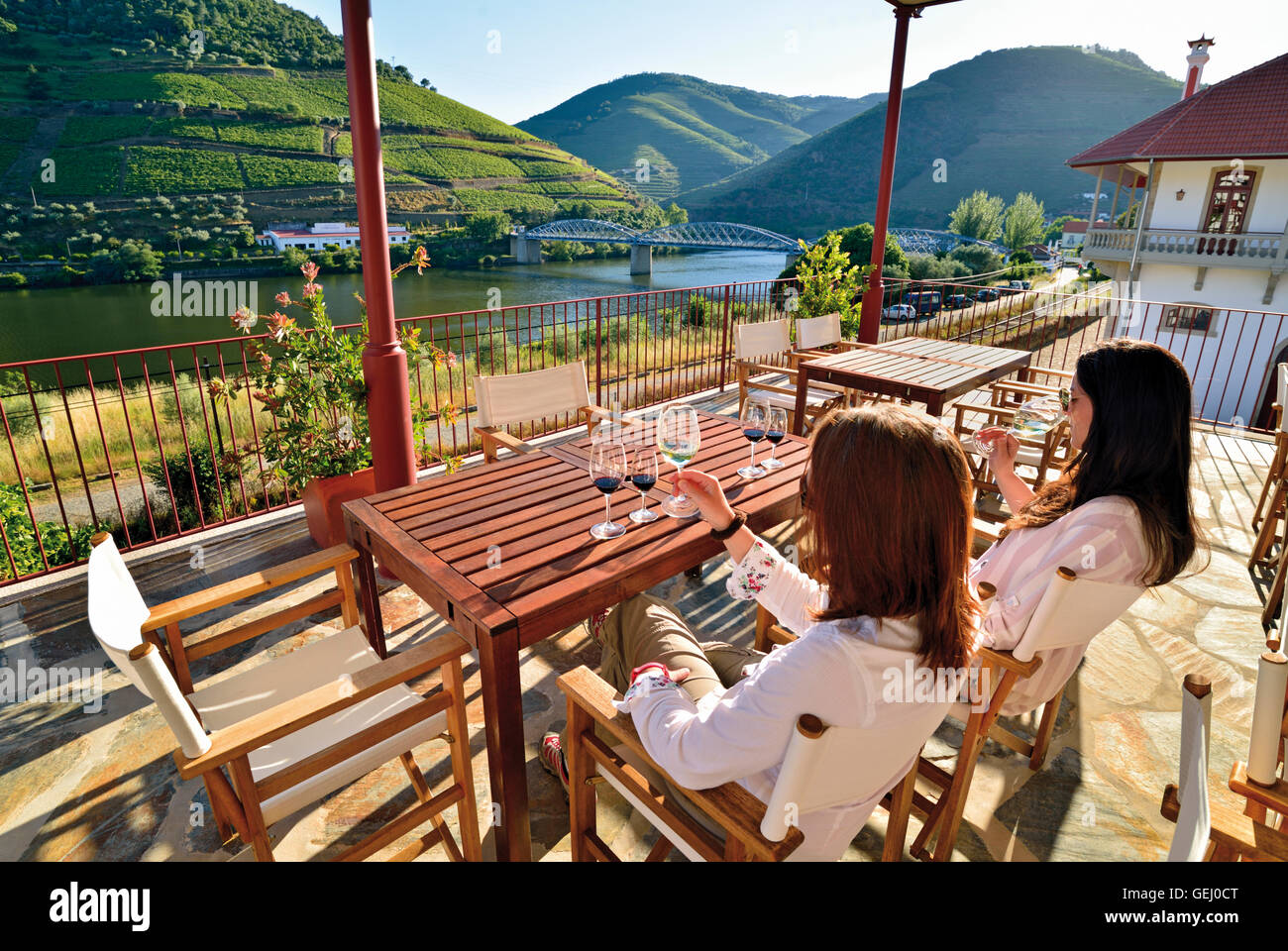 Portugal: Two women tasting wine at the terrace of Quinta do Bomfim with splendid view to the Douro river - Stock Image
