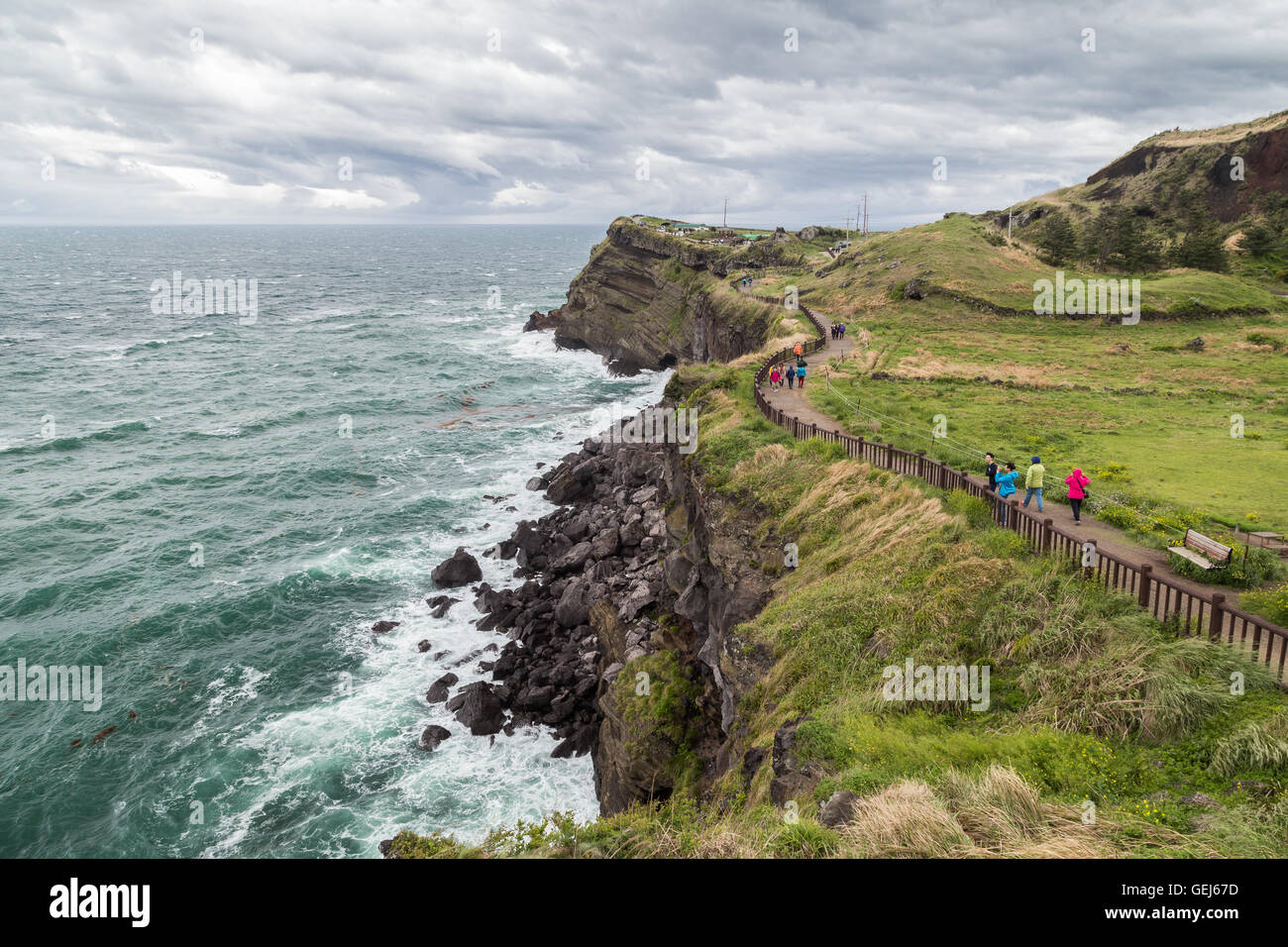 View of people and steep and rugged cliff next to the Songaksan Mountain on Jeju Island in South Korea. - Stock Image