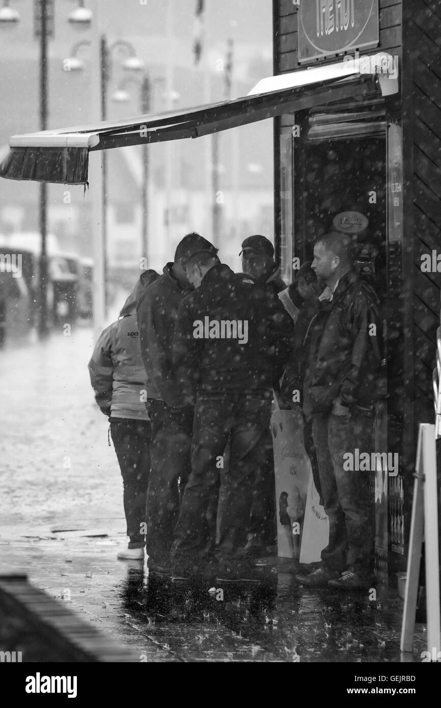 A group of people sheltering from heavy rain under a canopy - Stock Image