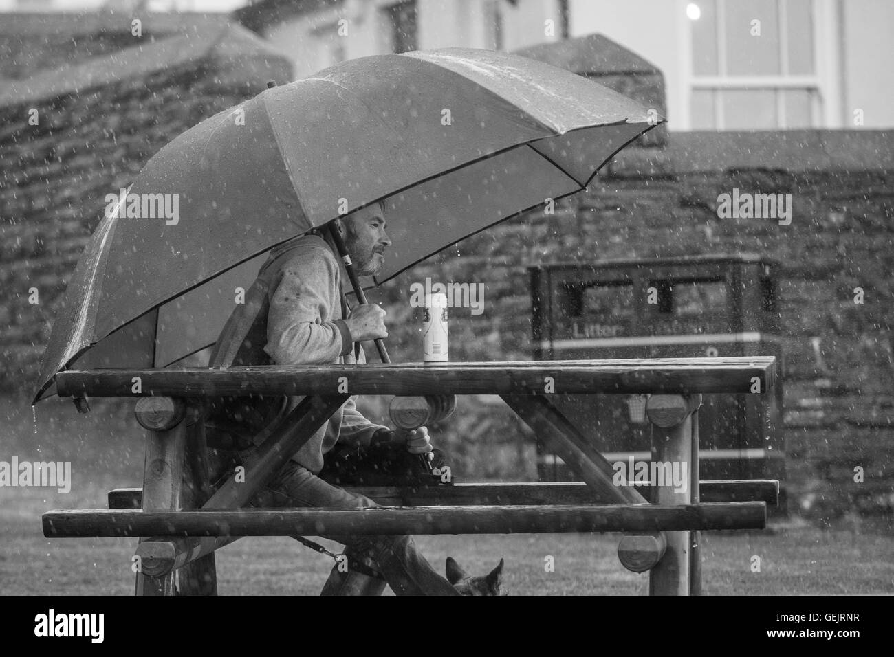 man sitting on a bench under a big umbrella while it is raining heavily - Stock Image