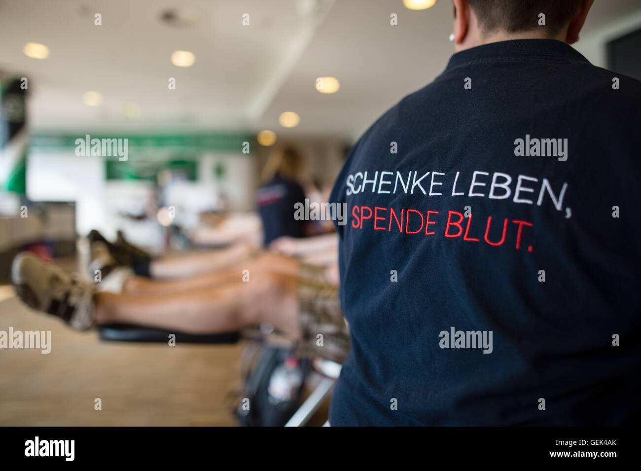 Hanover, Germany. 25th July, 2016. An assistant sits wearing a t-shirt written with 'give live, donate blood' - Stock Image