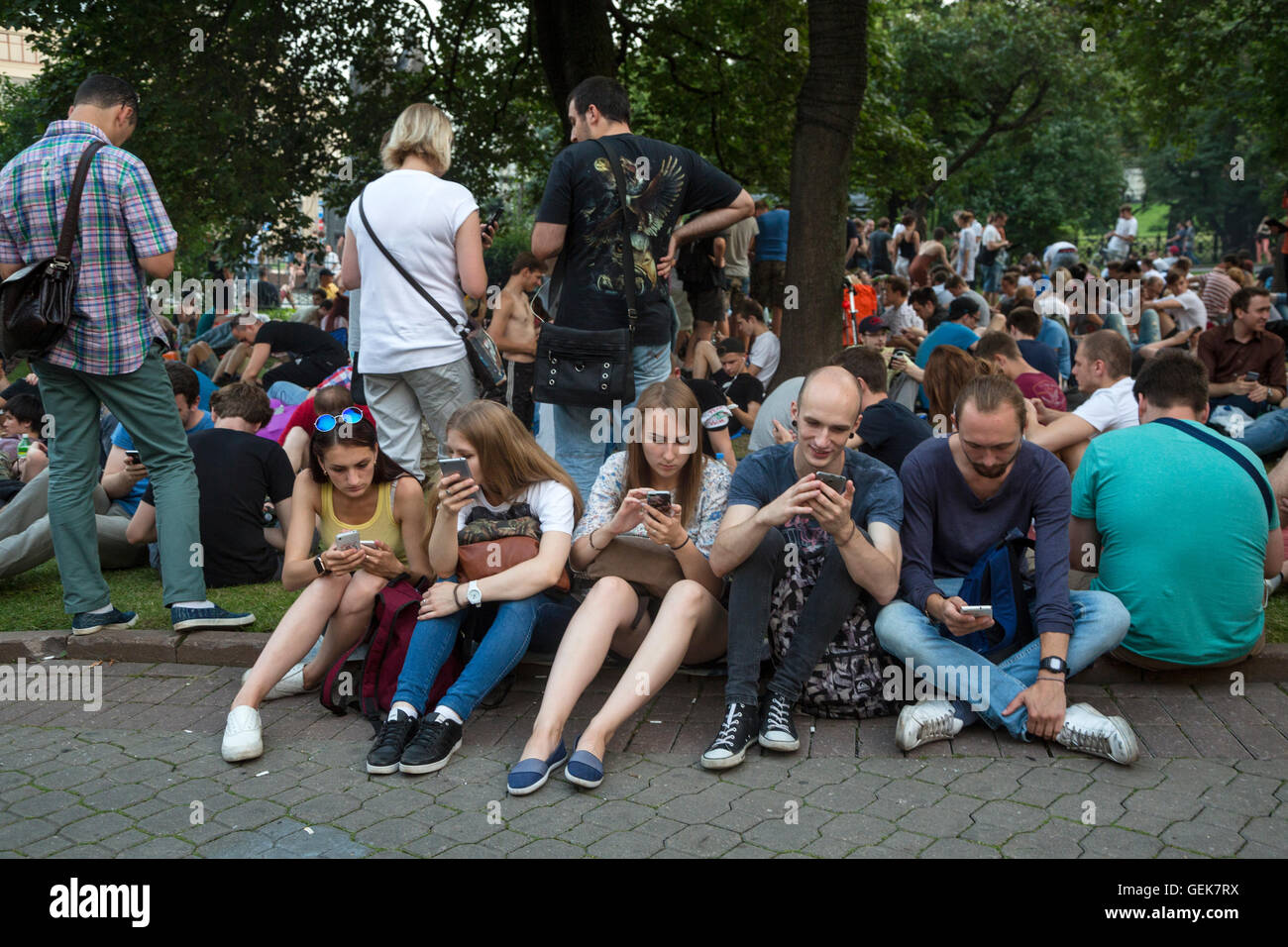 Moscow, Russia. 26 of July, 2016. Young people play Pokemon Go from Nintendo on their mobile devices in Ilyinsky - Stock Image