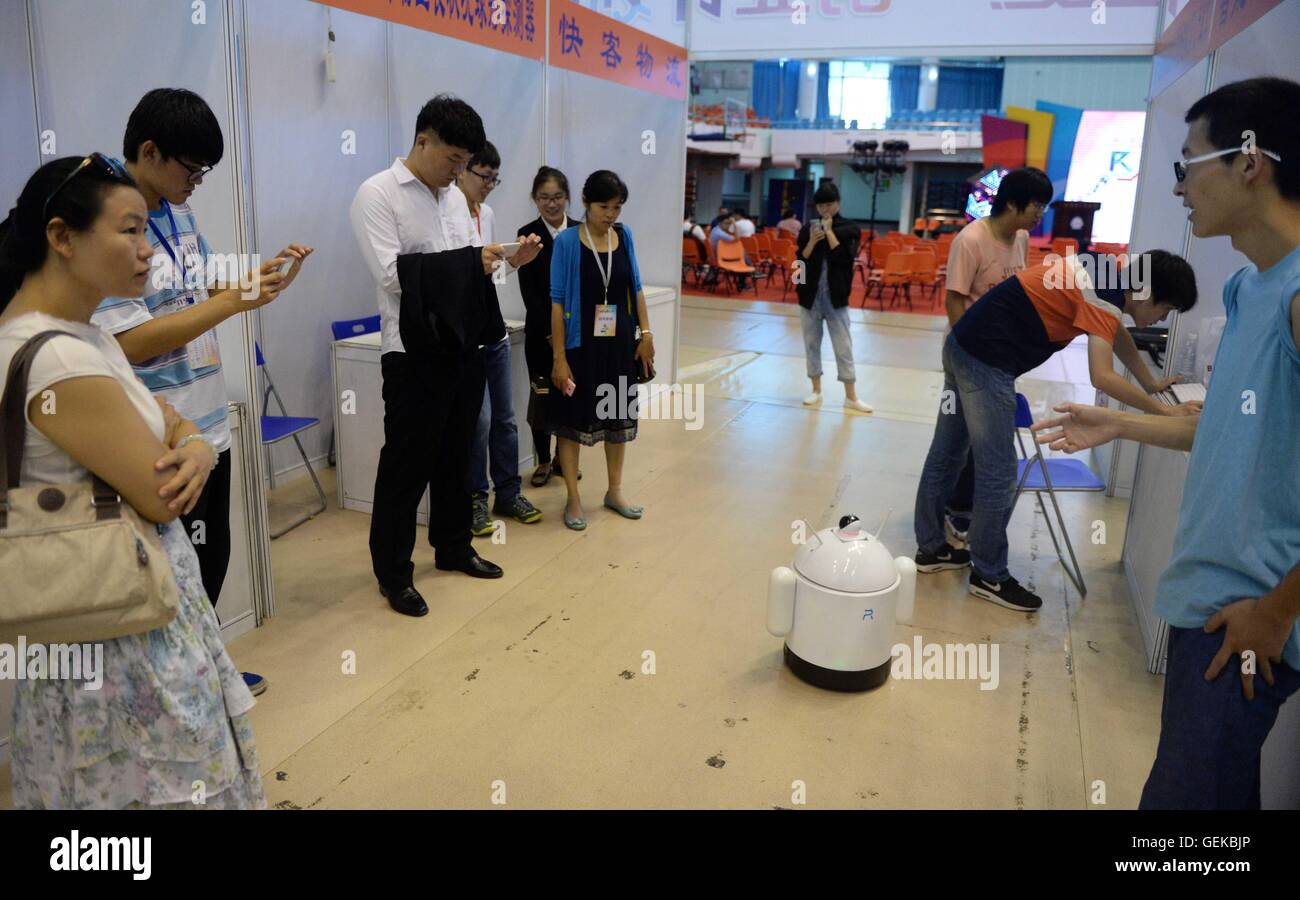 Harbin, China's Heilongjiang Province. 27th July, 2016. Visitors look at a multi-functional intelligent robot - Stock Image