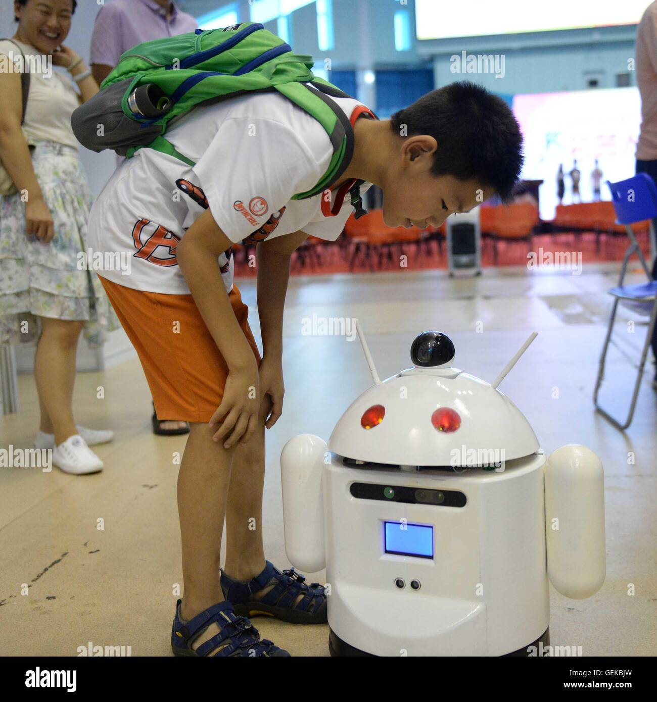Harbin, China's Heilongjiang Province. 27th July, 2016. A young boy looks at a multi-functional robot made by - Stock Image