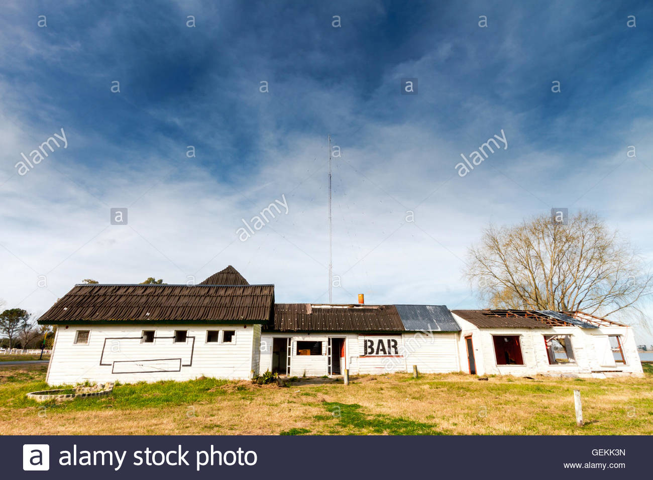 Abandoned front of a bar built with white woods with a lake behind - Stock Image