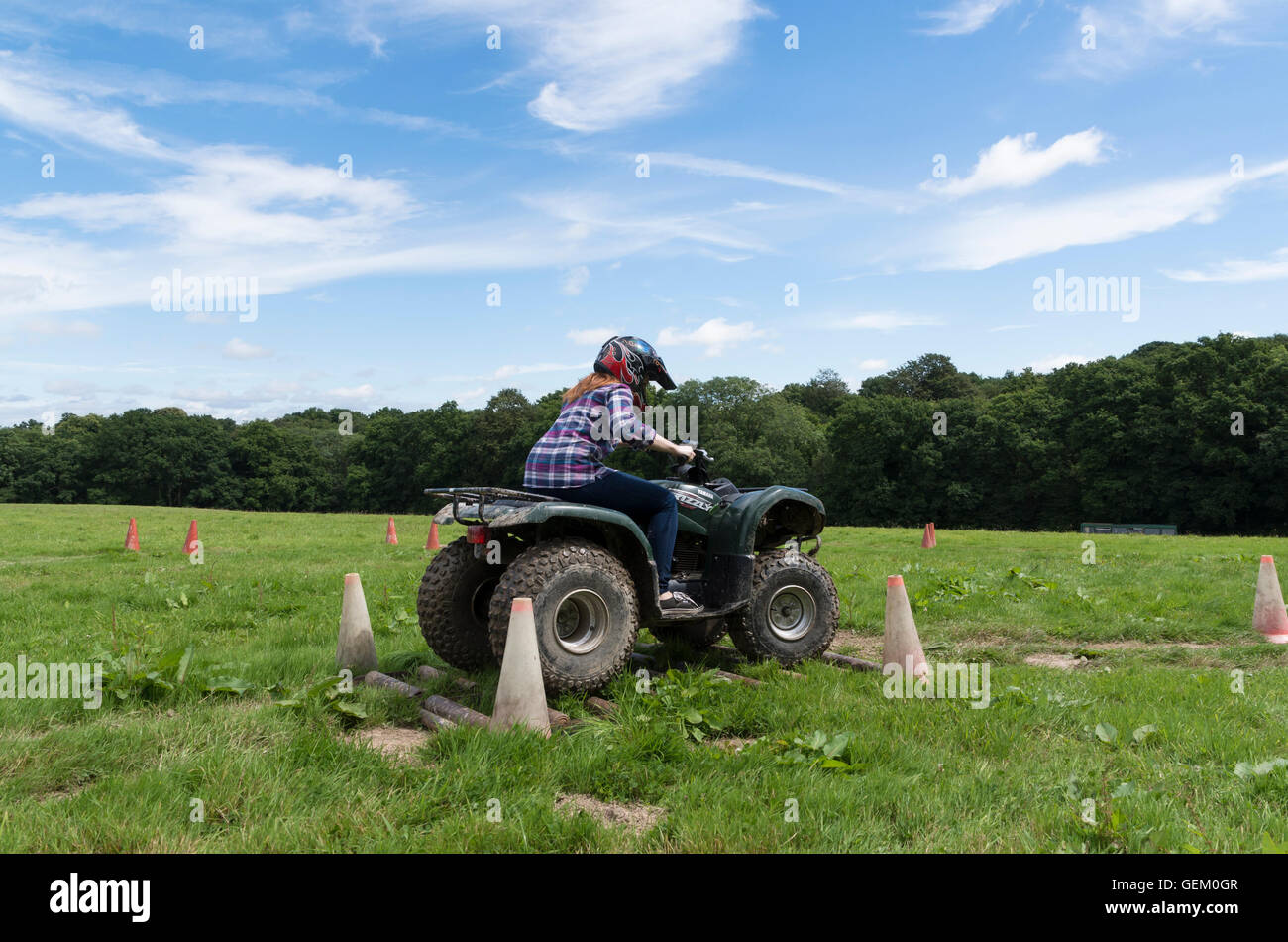Redhaired girl in check shirt riding a quad bike in the countryside through obstacles on an outdoor pursuits day - Stock Image