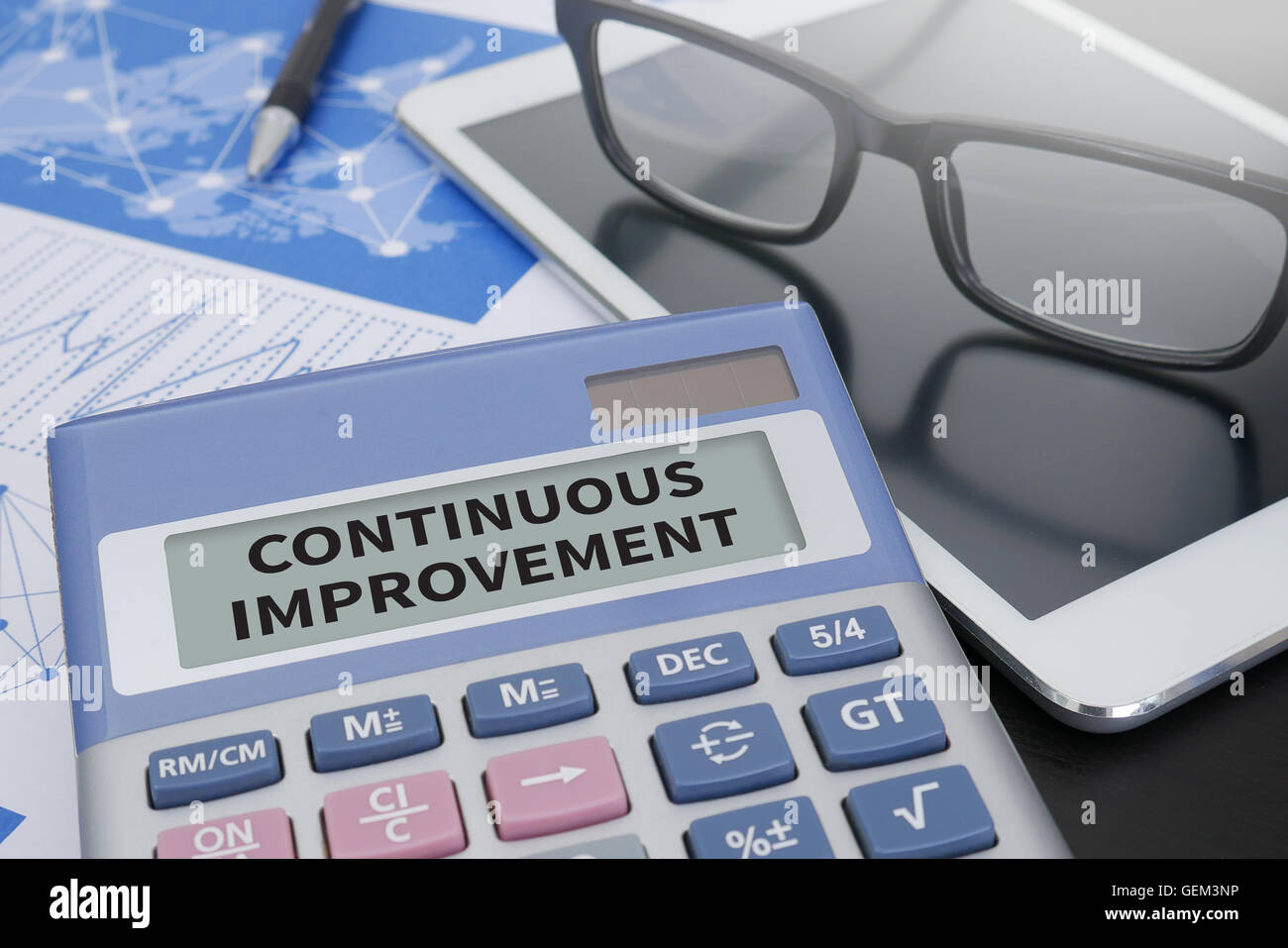 CONTINUOUS IMPROVEMENT Calculator  on table with Office Supplies. ipad - Stock Image