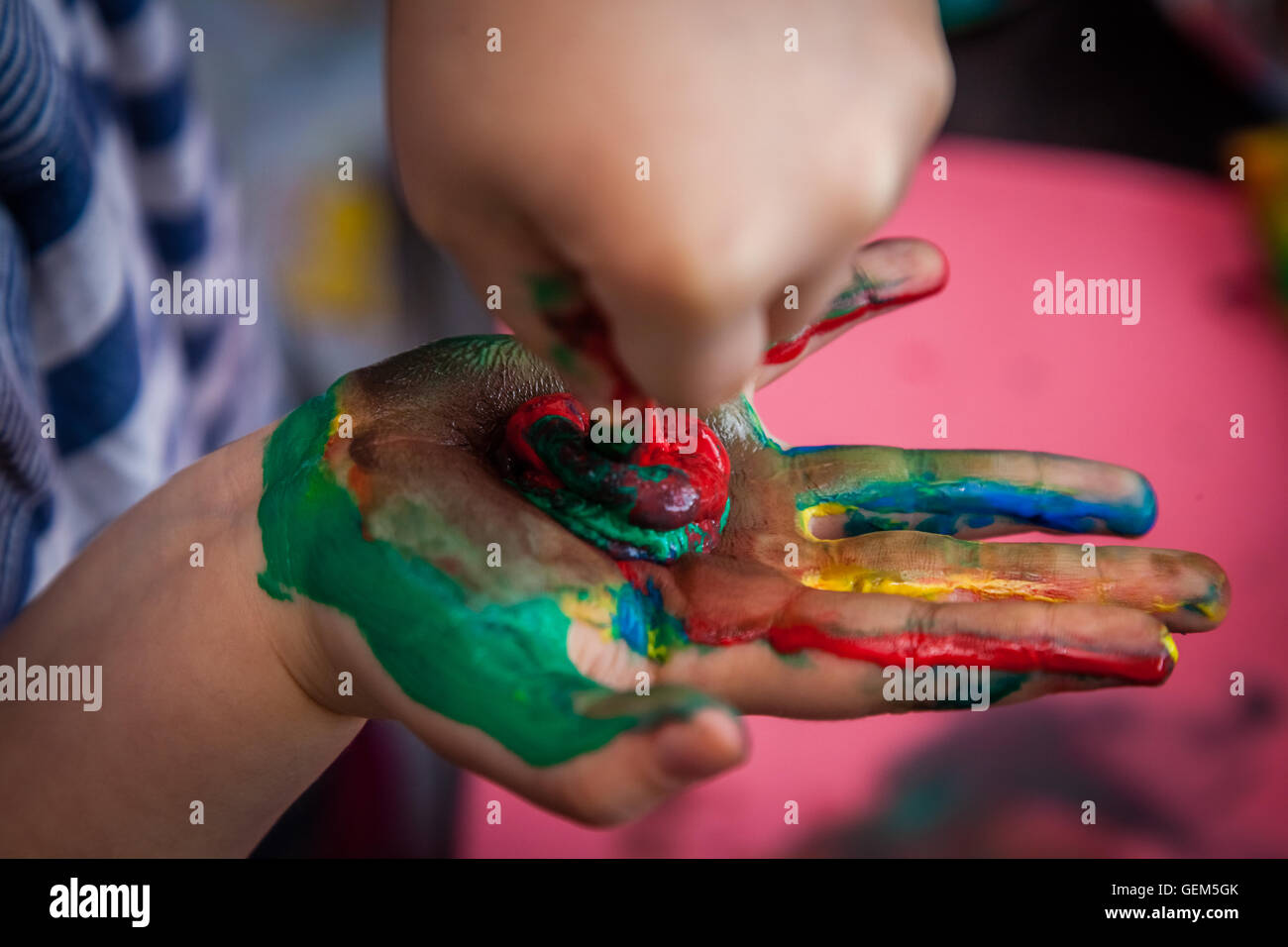 Child extracting more paint from the tube on his or her hand, already dirty from many colors - Stock Image
