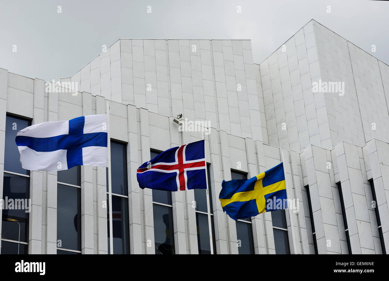 waving Finnish, Swedish, Icelandic flags against of The Finlandia Hall - Stock Image