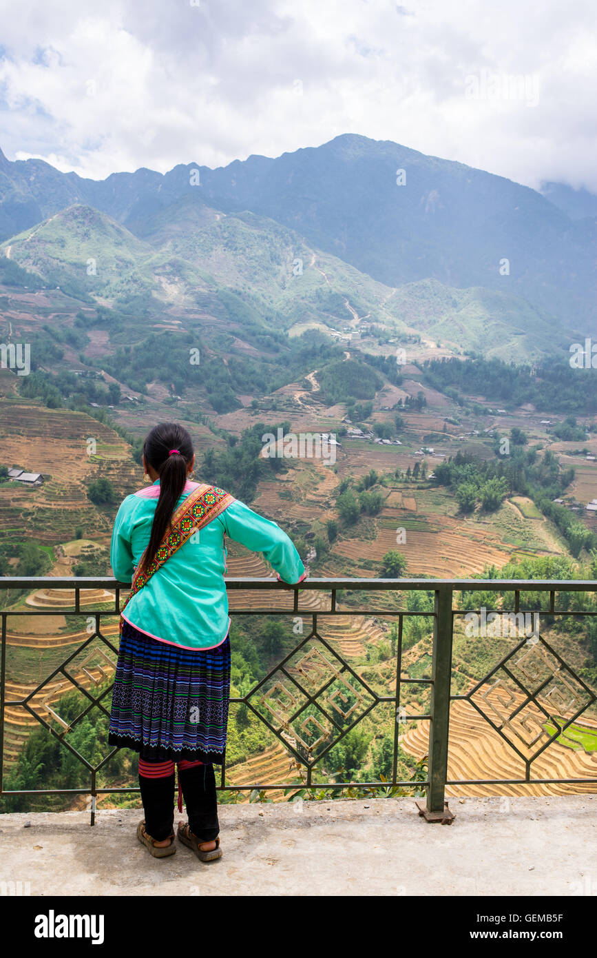 Vietnamese minority guide admiring the landscape with mountains and rice paddies in Sapa, North Vietnam. - Stock Image