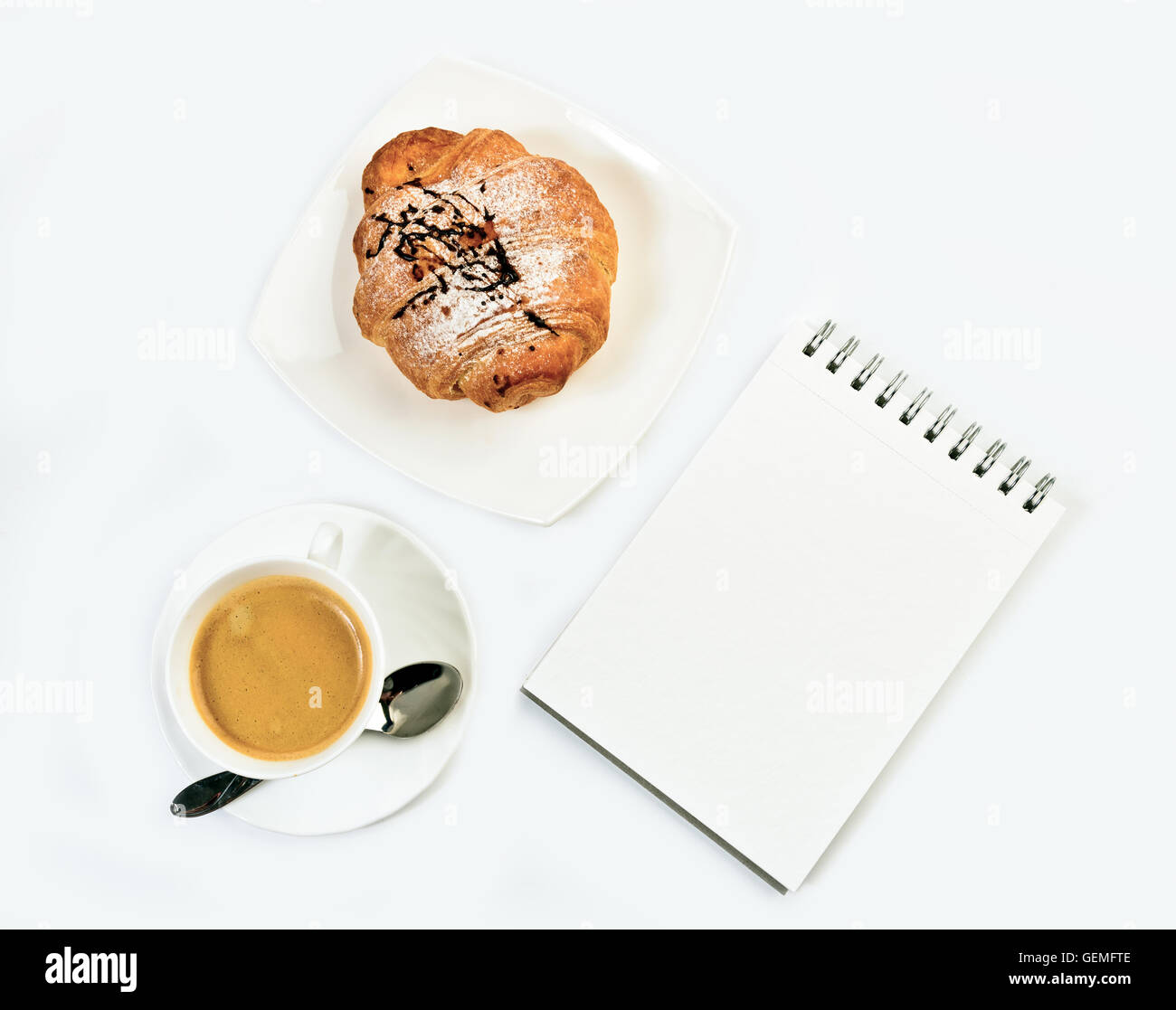 Fresh croissant, notepad  and coffee on white background. Top view. - Stock Image