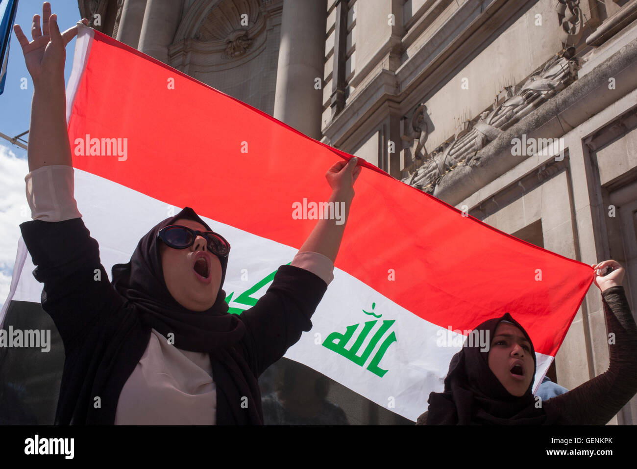 Two women holding the Iraqi flag shout their disapproval for former British Prime Minister Tony Blair on Chilcot - Stock Image