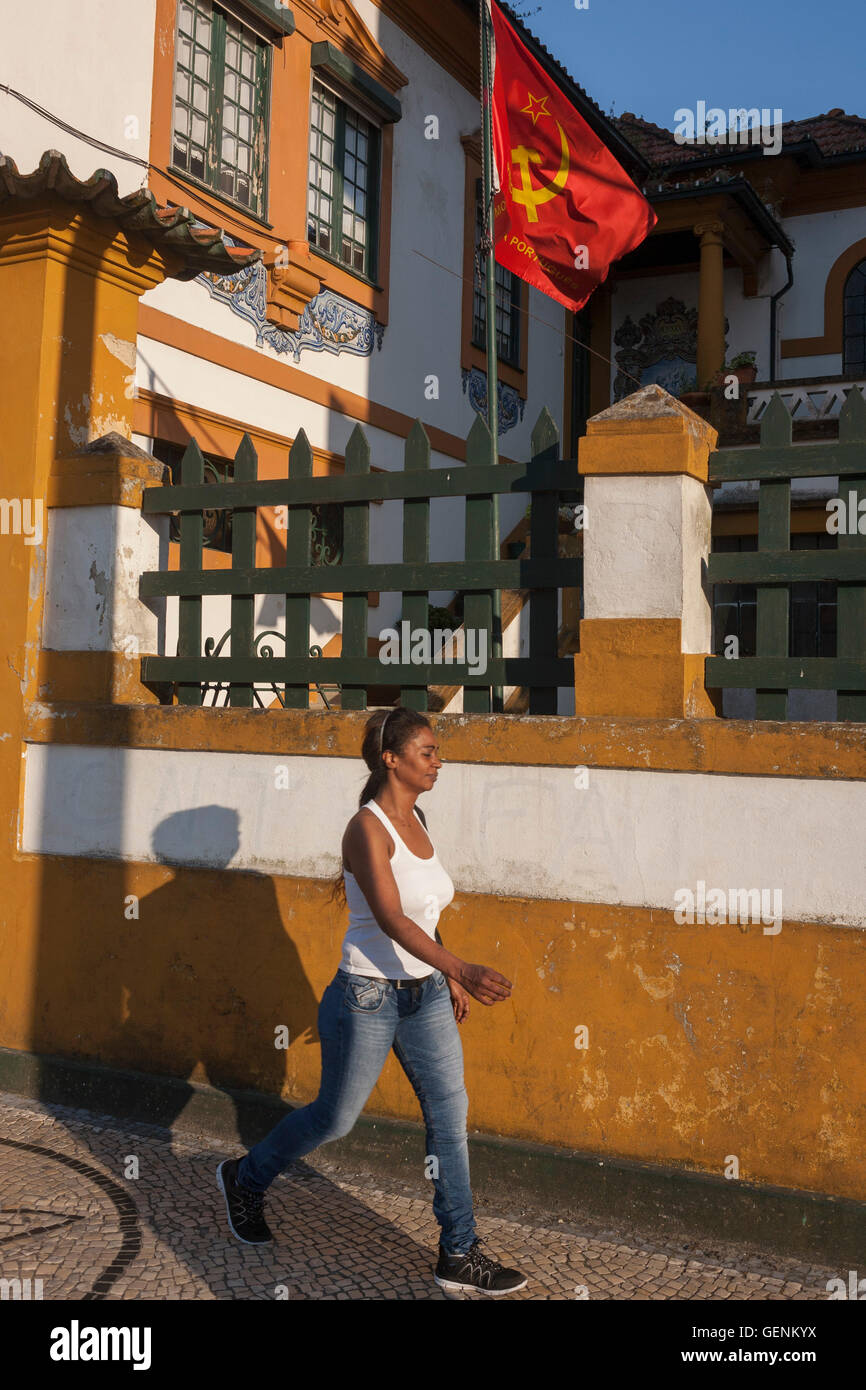A passer-by walks past the Communist party's regional offices on Avenida Dr. Lourenco Peixnho, in Aveiro, Portugal. - Stock Image