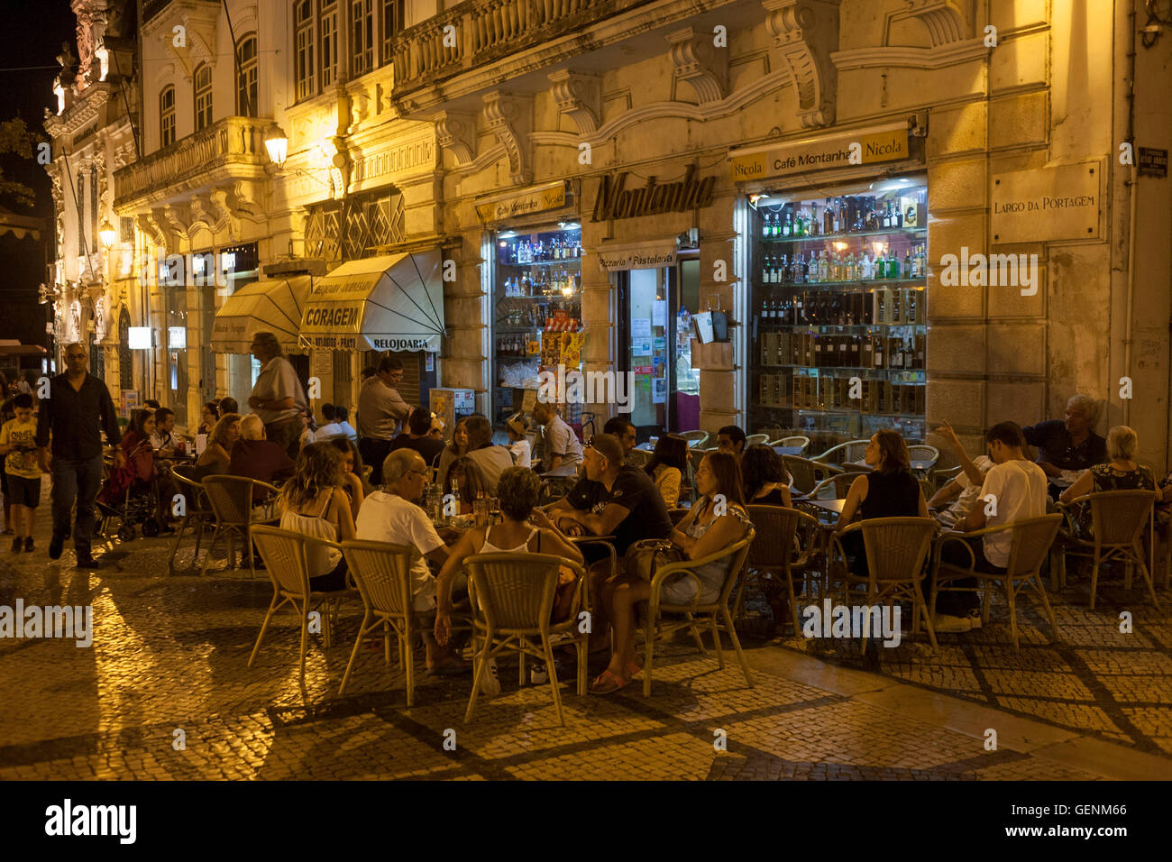 The busy Cafe Montanha in Largo da Portagem at night in Coimbra, Portugal. - Stock Image
