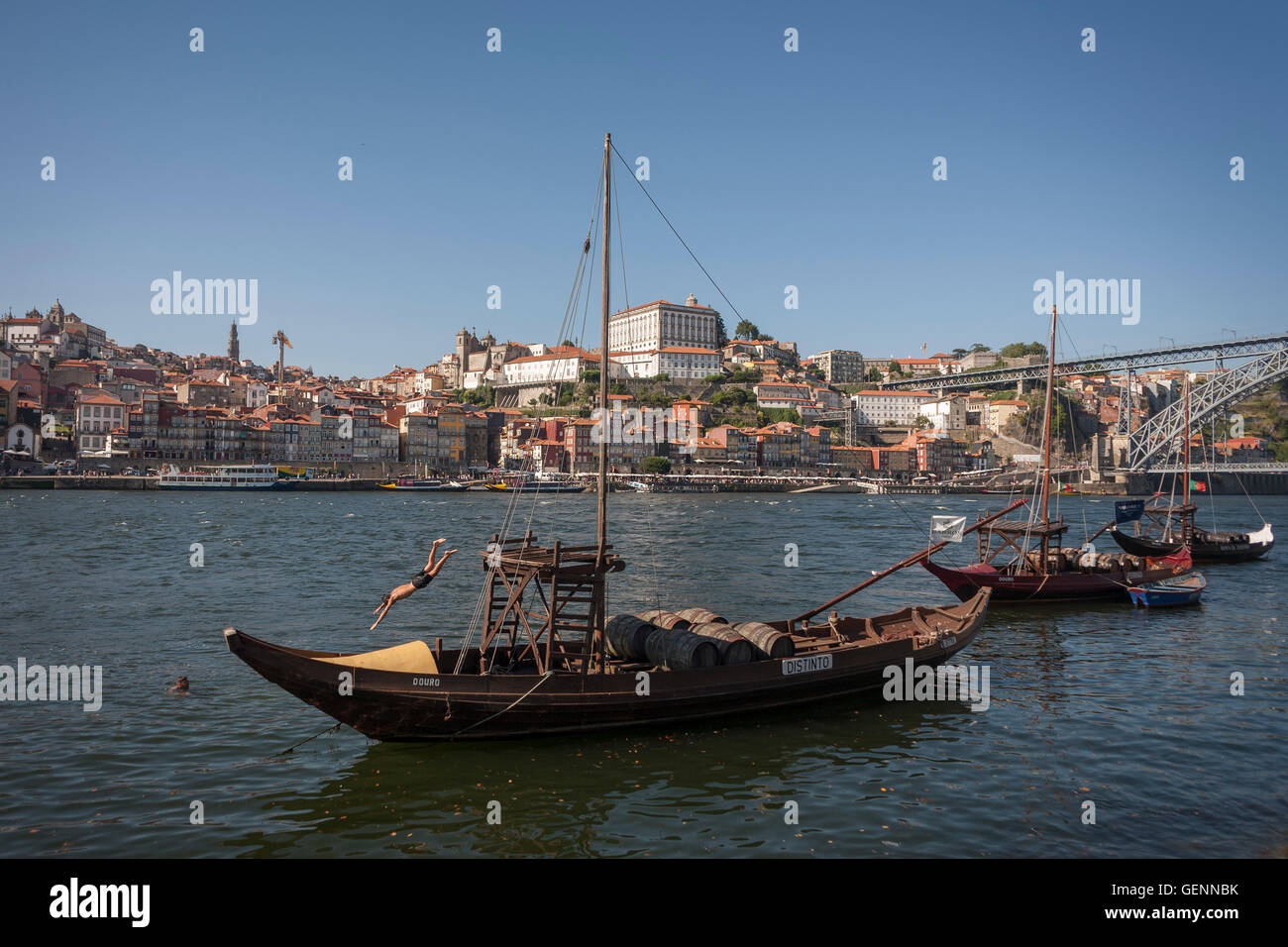 Local youth dives off a traditional Rabelo boat (Port wine transporter), into the River Douro in Porto, Portugal. Stock Photo