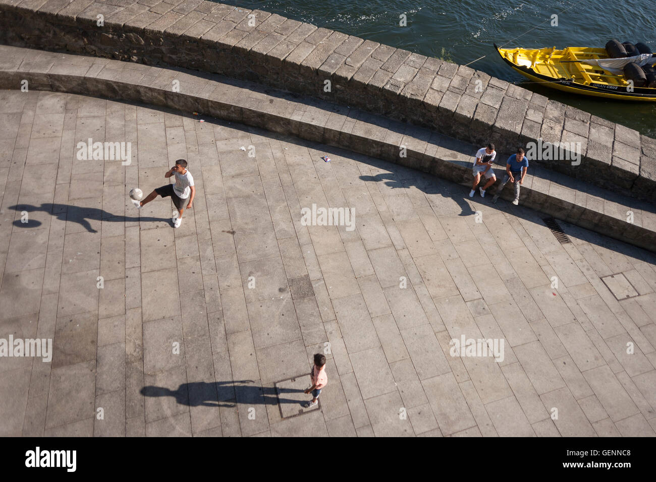 Aerial view of young men during a kickabout on the riverfront of the Douro in Porto, Portugal. Stock Photo