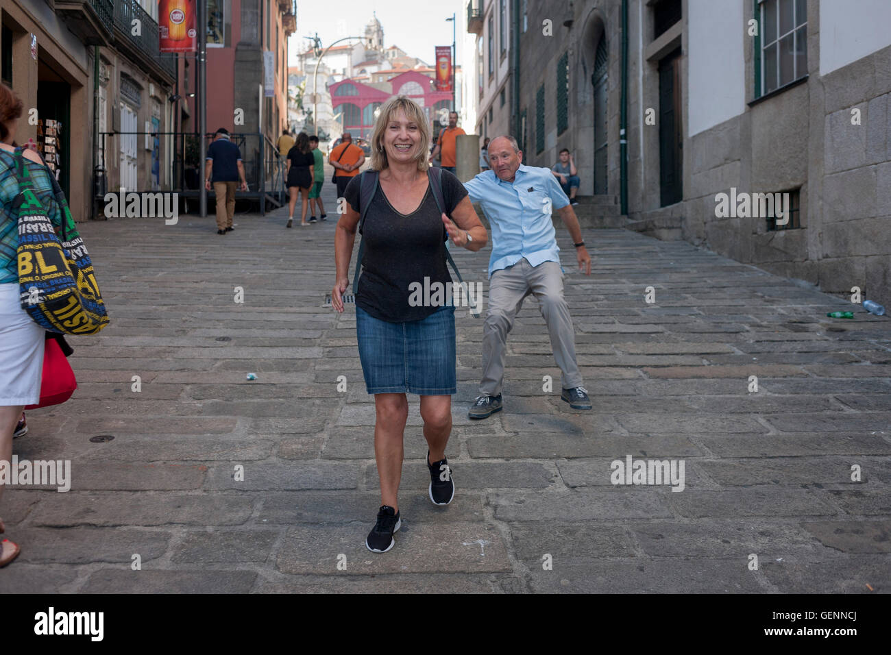 Middle-aged couple mess about with a backwards running race on a hill, while on holiday in Porto, Portugal: A sequence - Stock Image