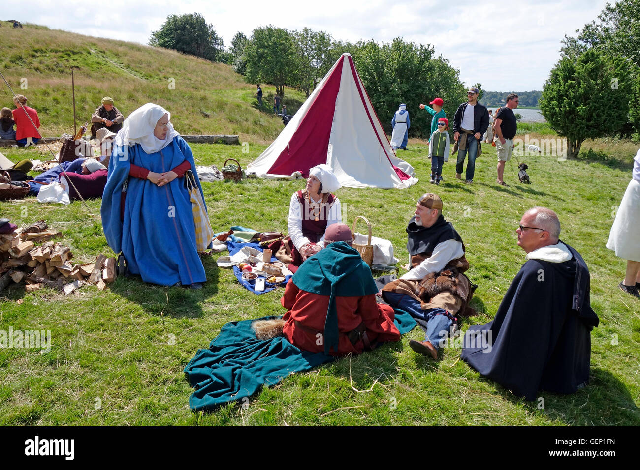 People dressed in medieval robes have picnic on lawn. Re-enactment, Halland . Sweden - Stock Image