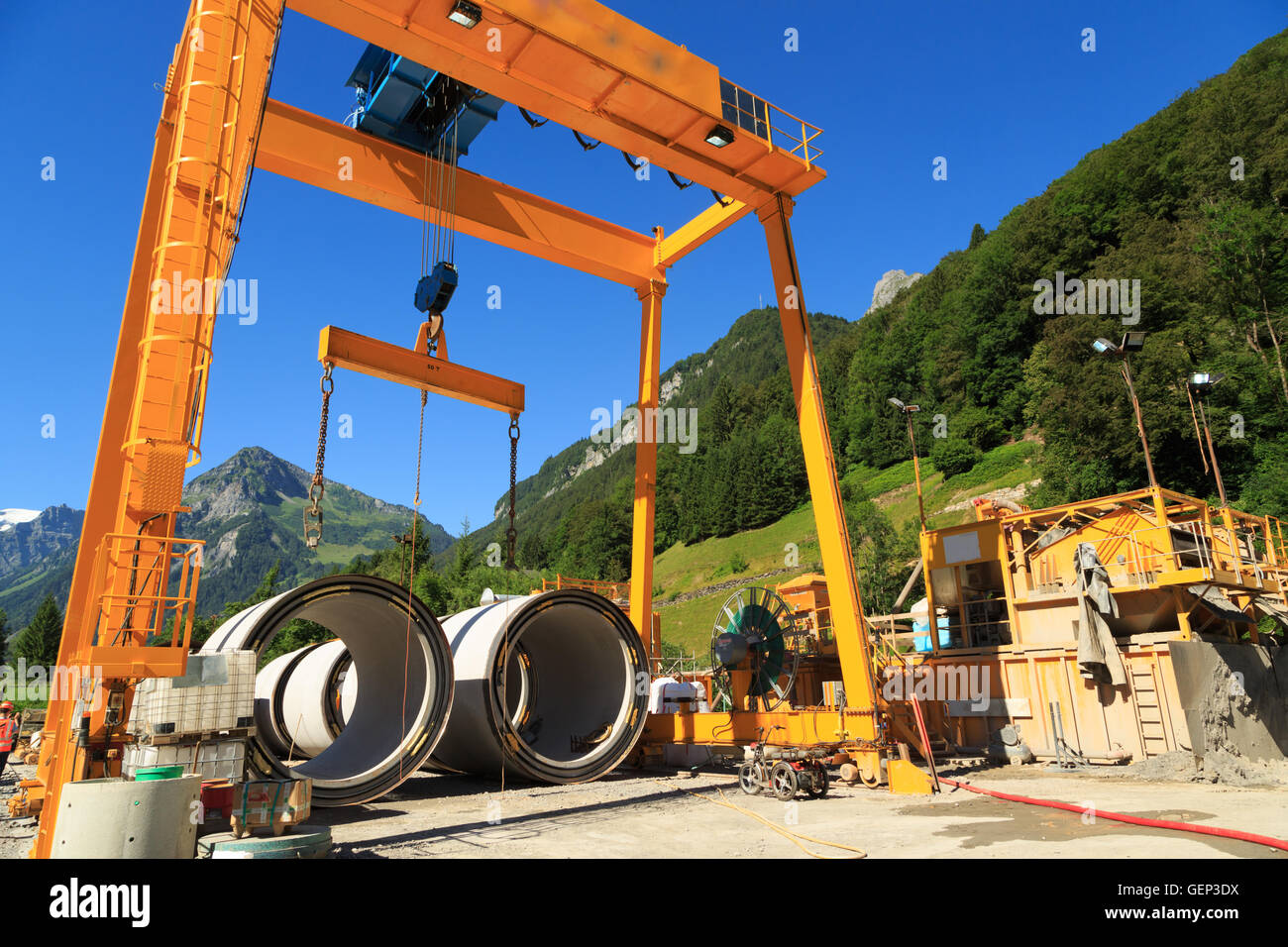 A photograph of a construction crane for a micro-tunneling (microtunneling) project in the alpine region of Switzerland. - Stock Image