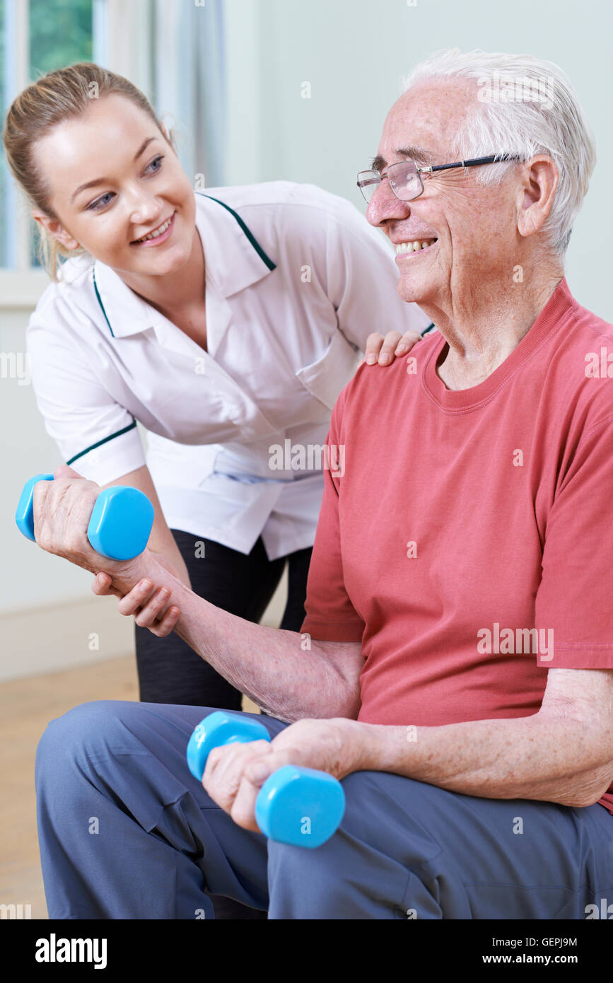 Senior Male Working With Physiotherapist Using Weights - Stock Image