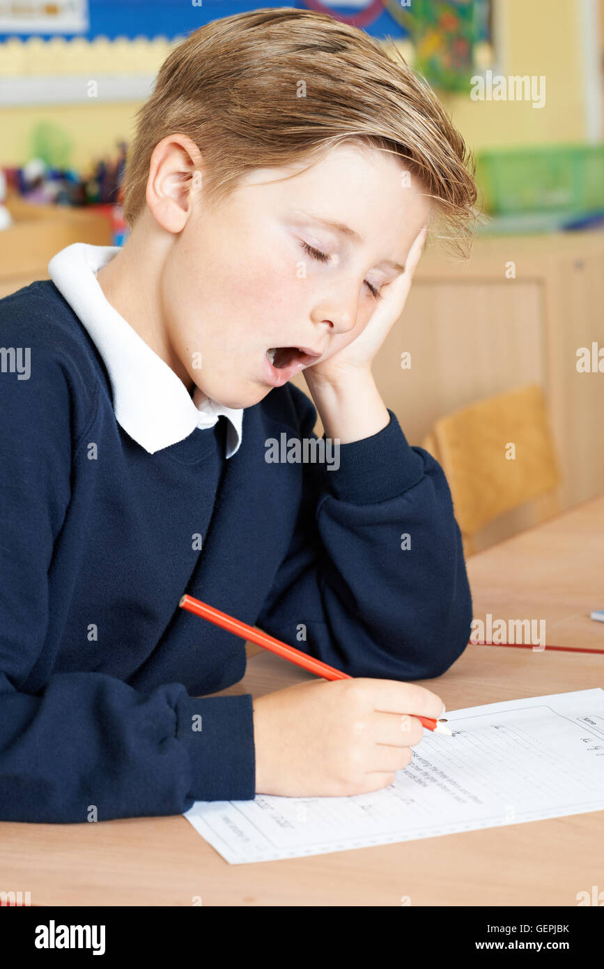 Male Elementary School Pupil Yawning In Classroom - Stock Image