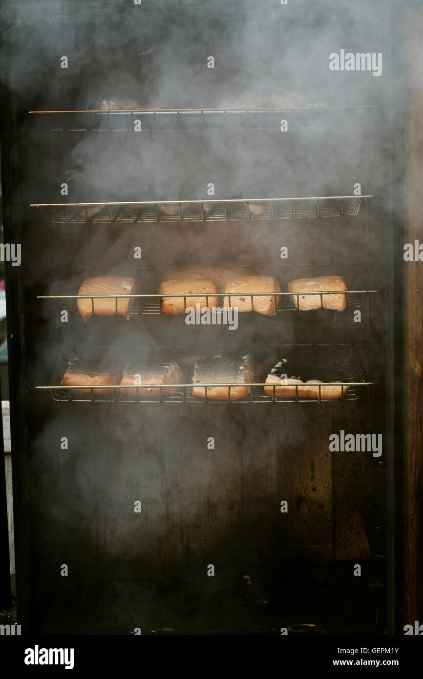 Fish fillets on racks in a fish smoker. - Stock Image