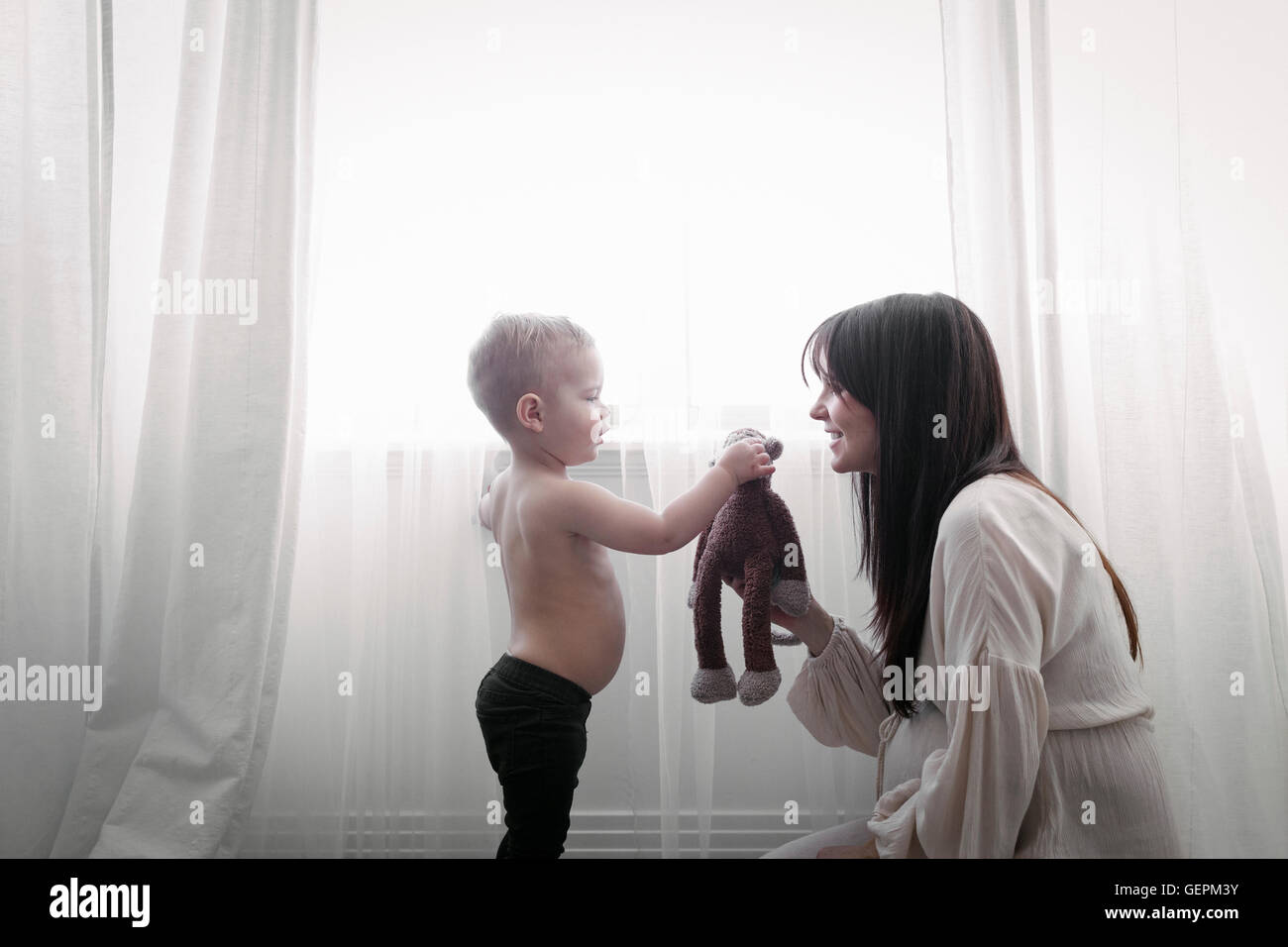 A heavily pregnant woman playing with her young son. - Stock Image