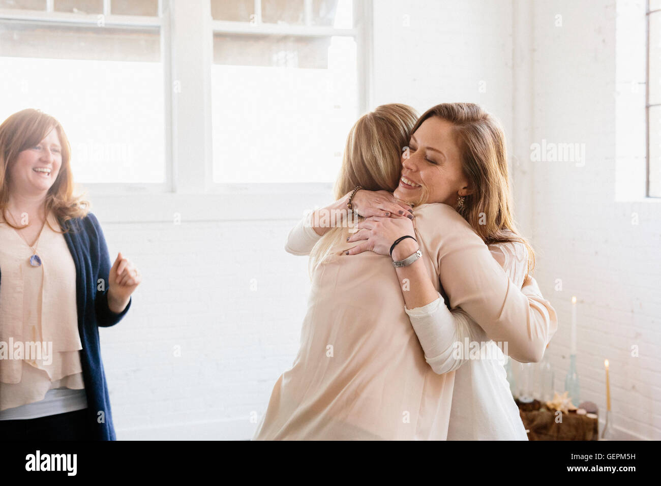 Two woman hugging at a party. - Stock Image