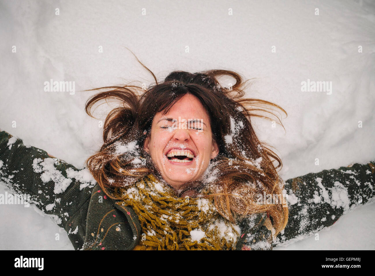 A woman lying on a snow bank with her arms stretched out. - Stock Image