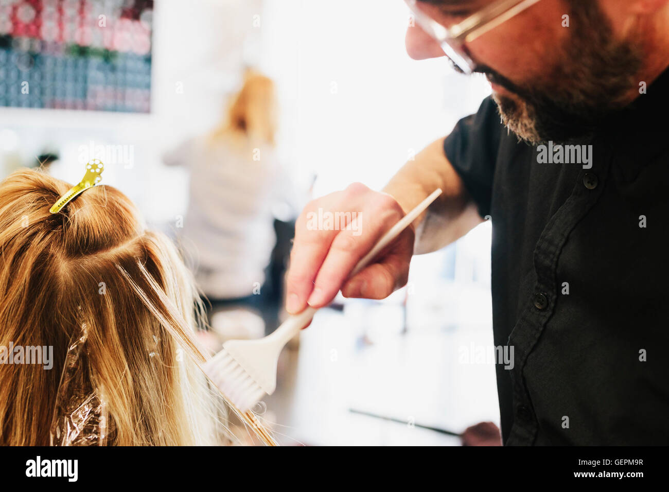 A hair colourist, a man using a paintbrush to cover sections of a woman's blonde hair. - Stock Image