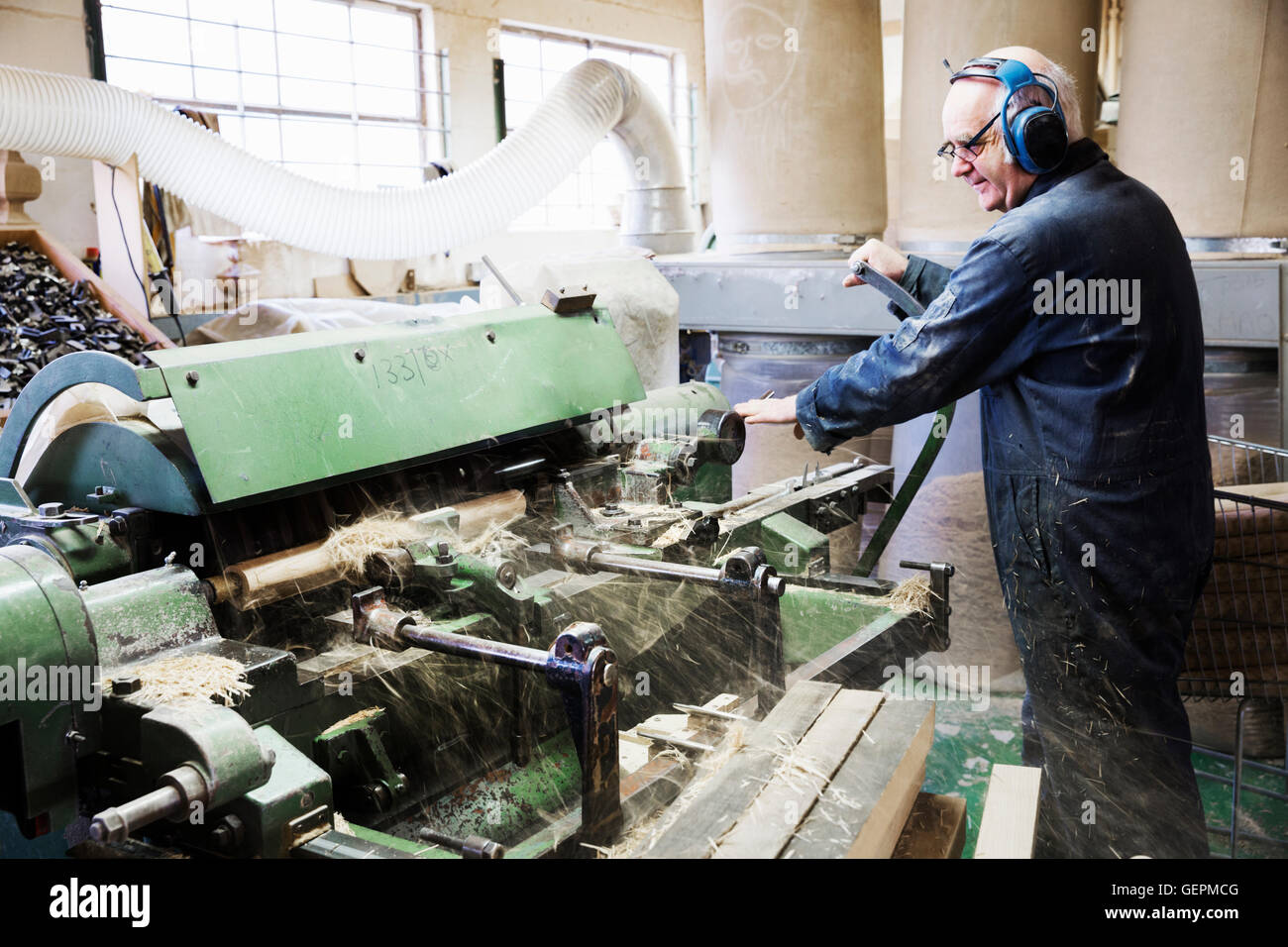 Man standing in a carpentry workshop, wearing hearing protectors, working at a woodworking machine. - Stock Image