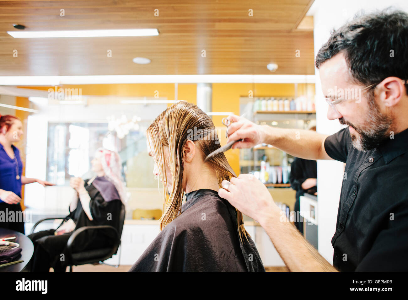 A hair stylist with a client, combing her long hair in sections. - Stock Image