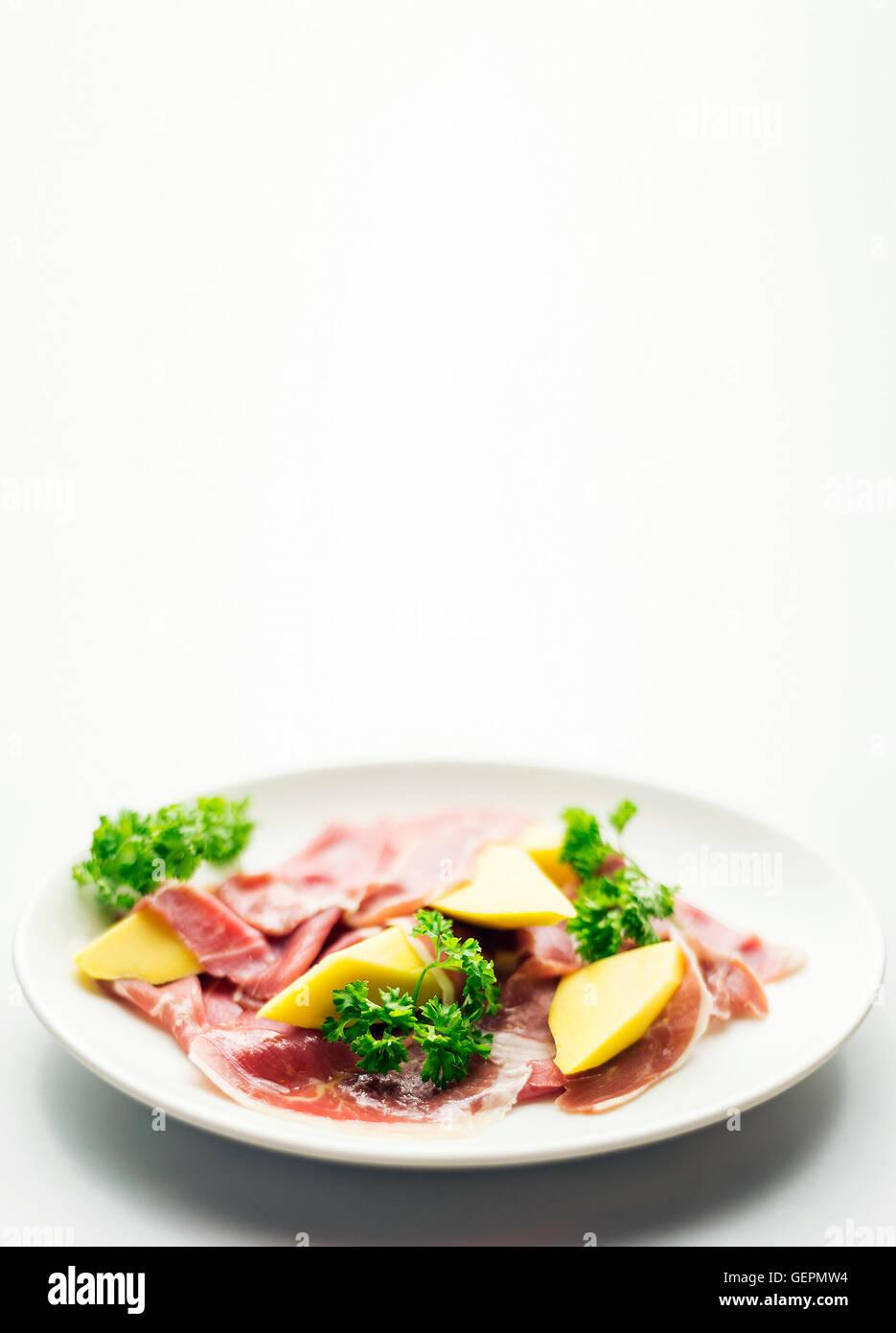 cured parma serrano style ham with fresh mango salad snack starter - Stock Image