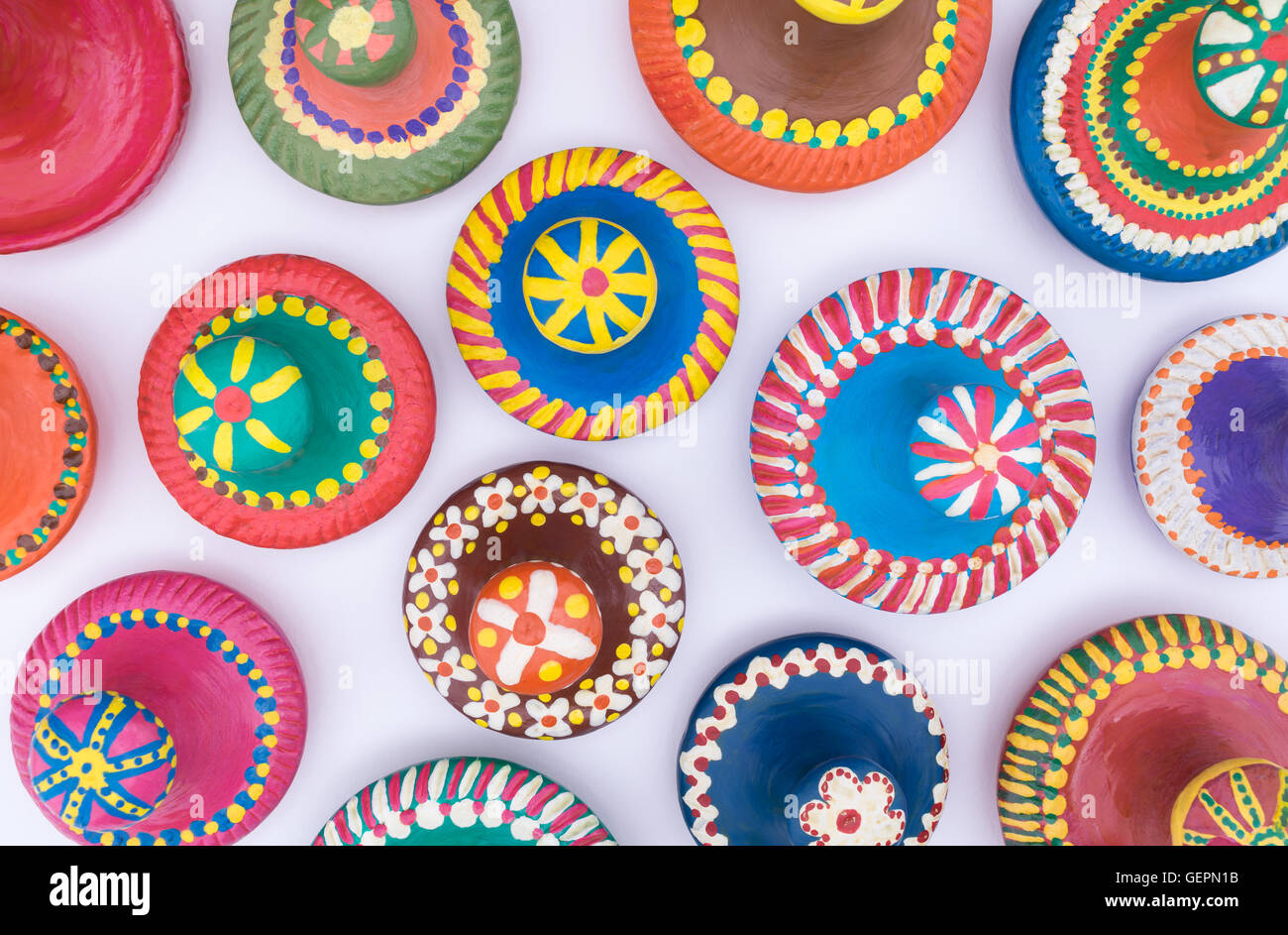 Composition of painted handmade pottery lids on white background - Stock Image