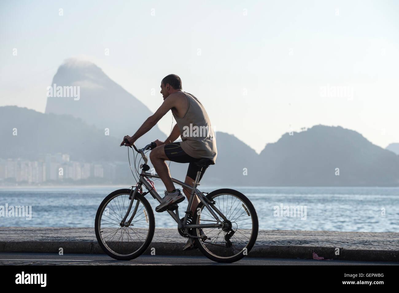 RIO DE JANEIRO - APRIL 3, 2016: Young Brazilian man rides a bicycle on the beachfront boardwalk at Copacabana Beach. - Stock Image
