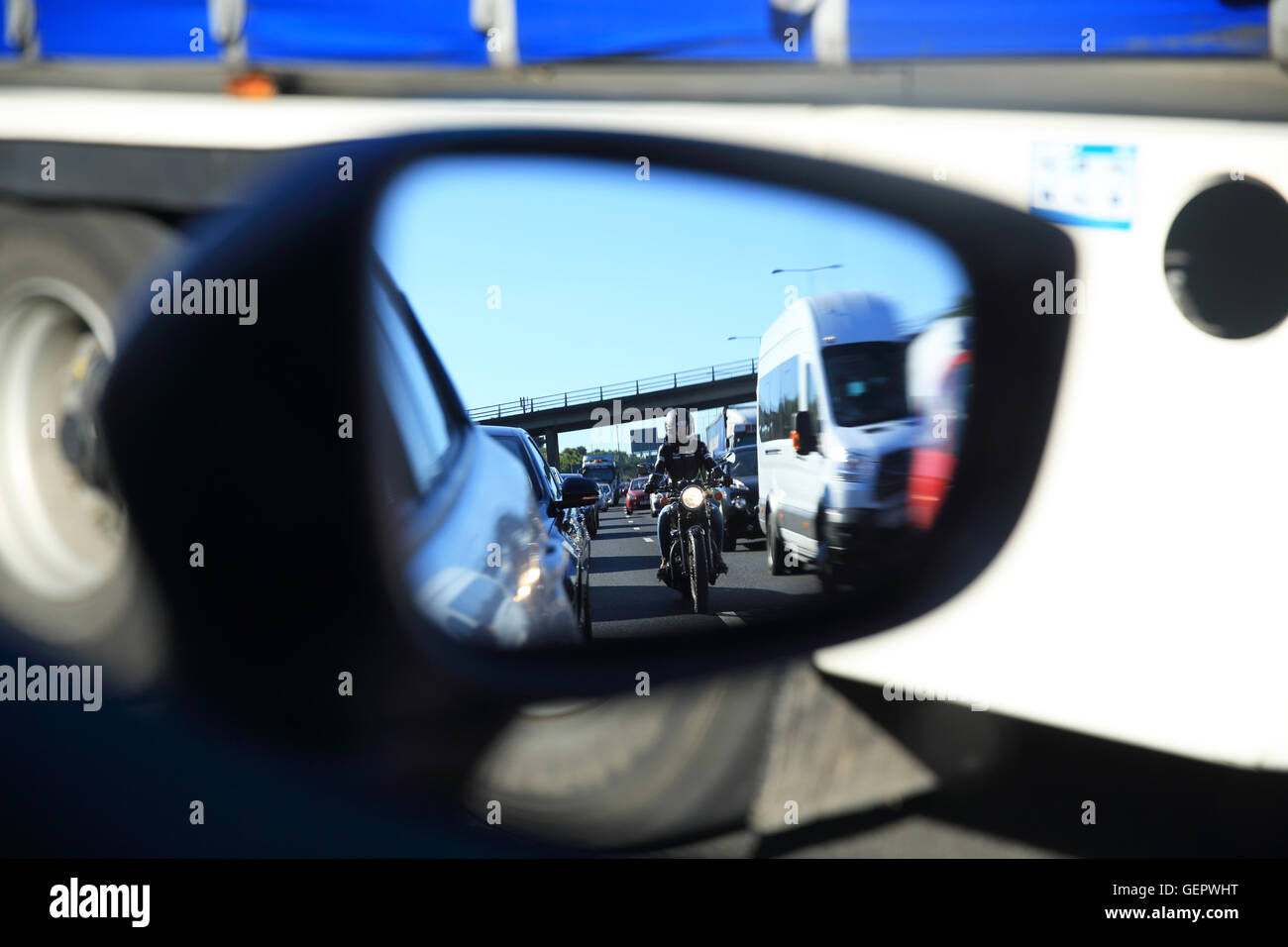 Heavy traffic on the M25, seen in a wing mirror, in Kent, England, UK - Stock Image