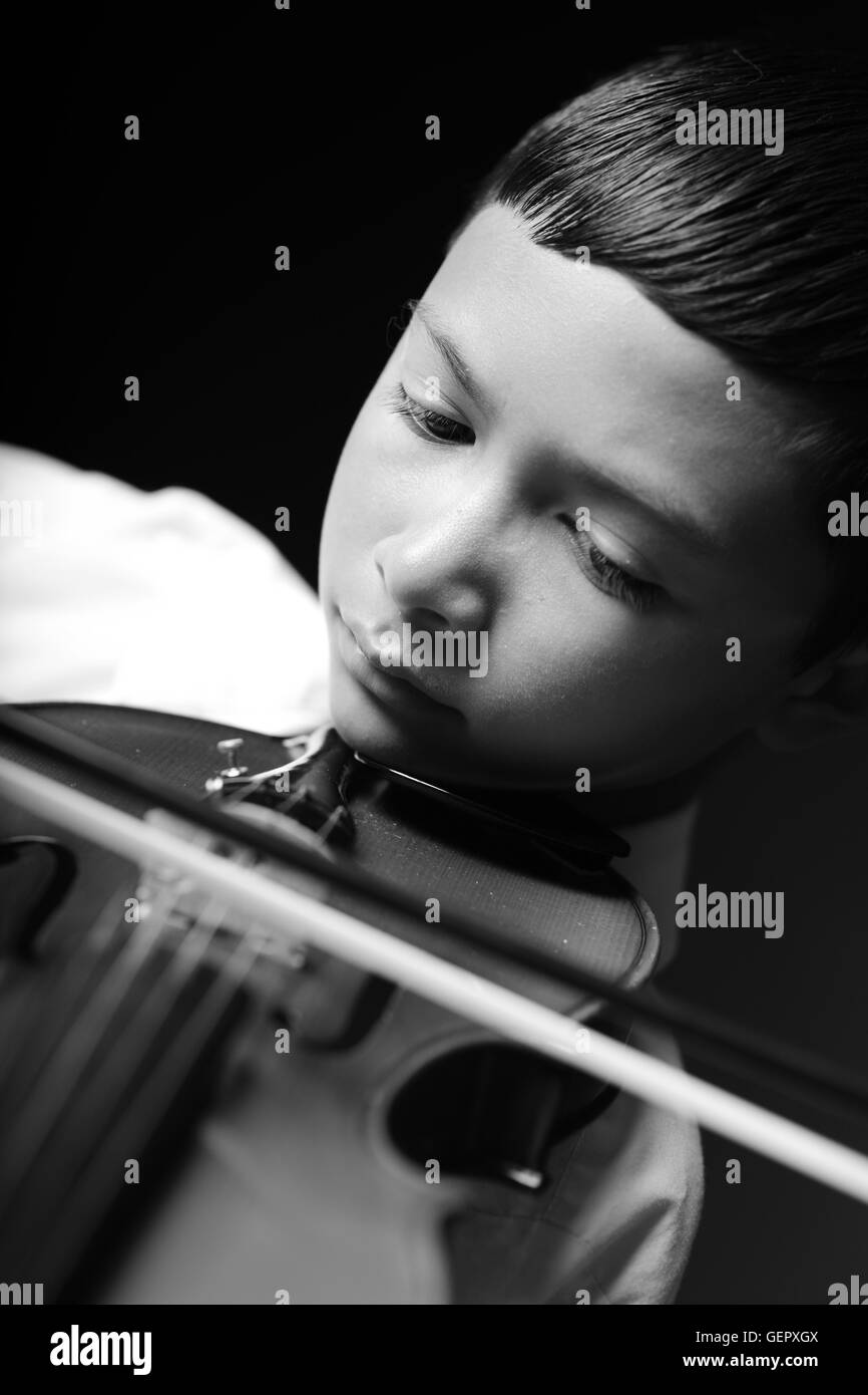 Black and White portrait of a boy playing violin Stock Photo