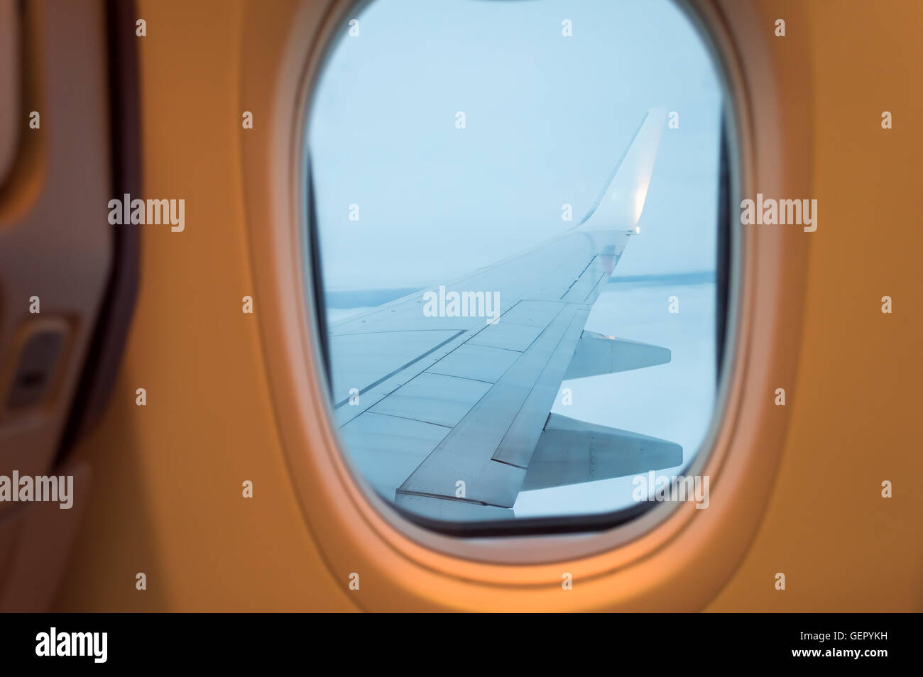 Airplane wing out of window Stock Photo