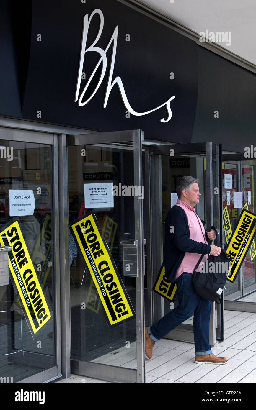A customer leaving a BHS store with 'Store Closing' signs on the door in Princes Street, Edinburgh, Scotland, - Stock Image