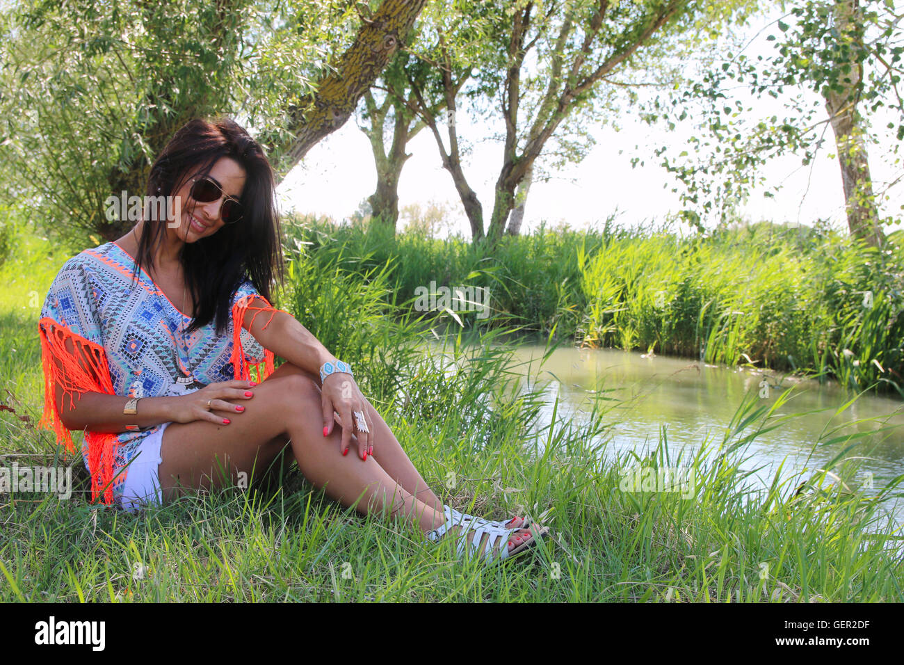 Beautiful woman wearing a tunic next to a river - Stock Image