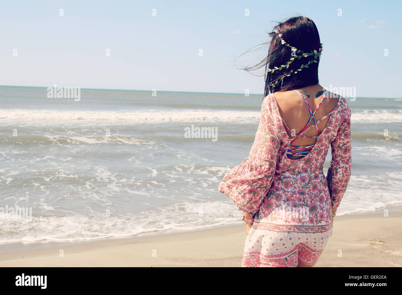 Beautiful woman wearing a tunic next to the sea - Stock Image
