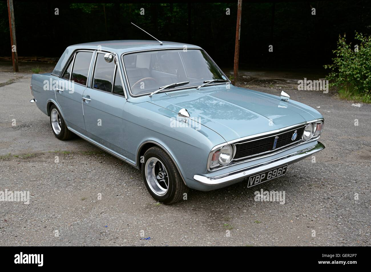 A Sixties Ford Cortina MkII saloon stands on concrete in front of an old covered shed - Stock Image