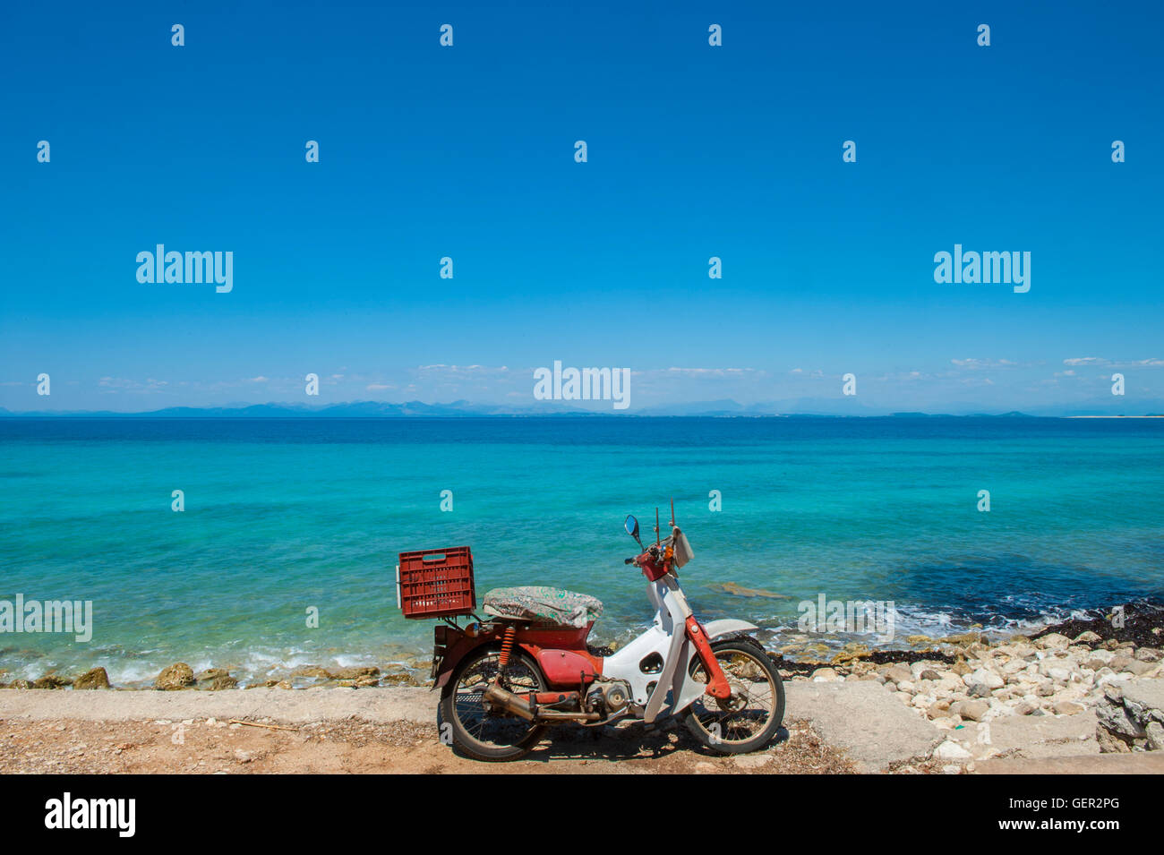 A lone, old moped on a deserted beach in Greece - Stock Image