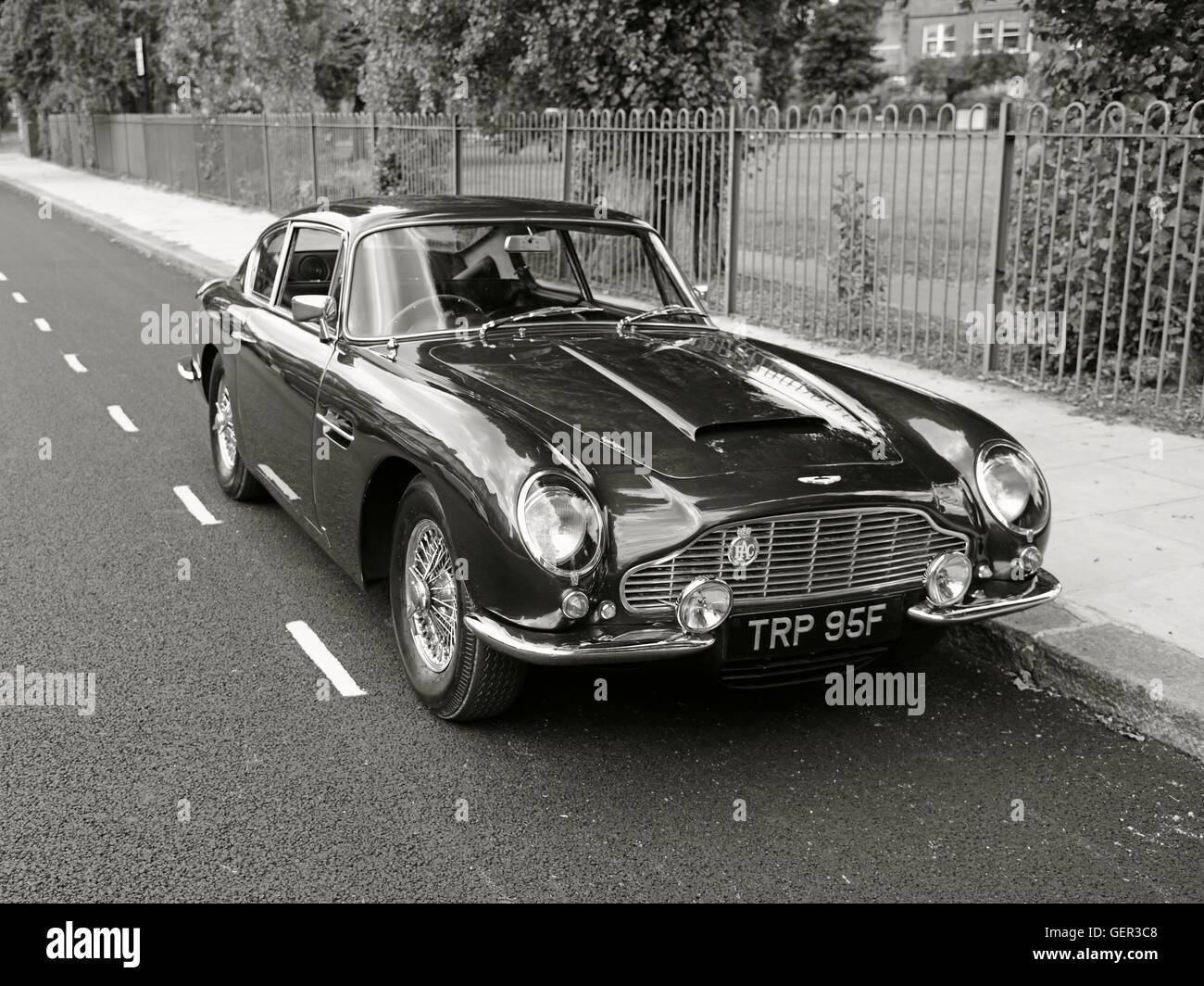 Black and white shot of Aston Martin DB6 classic car parked on suburban street by railings with a park beyond - Stock Image