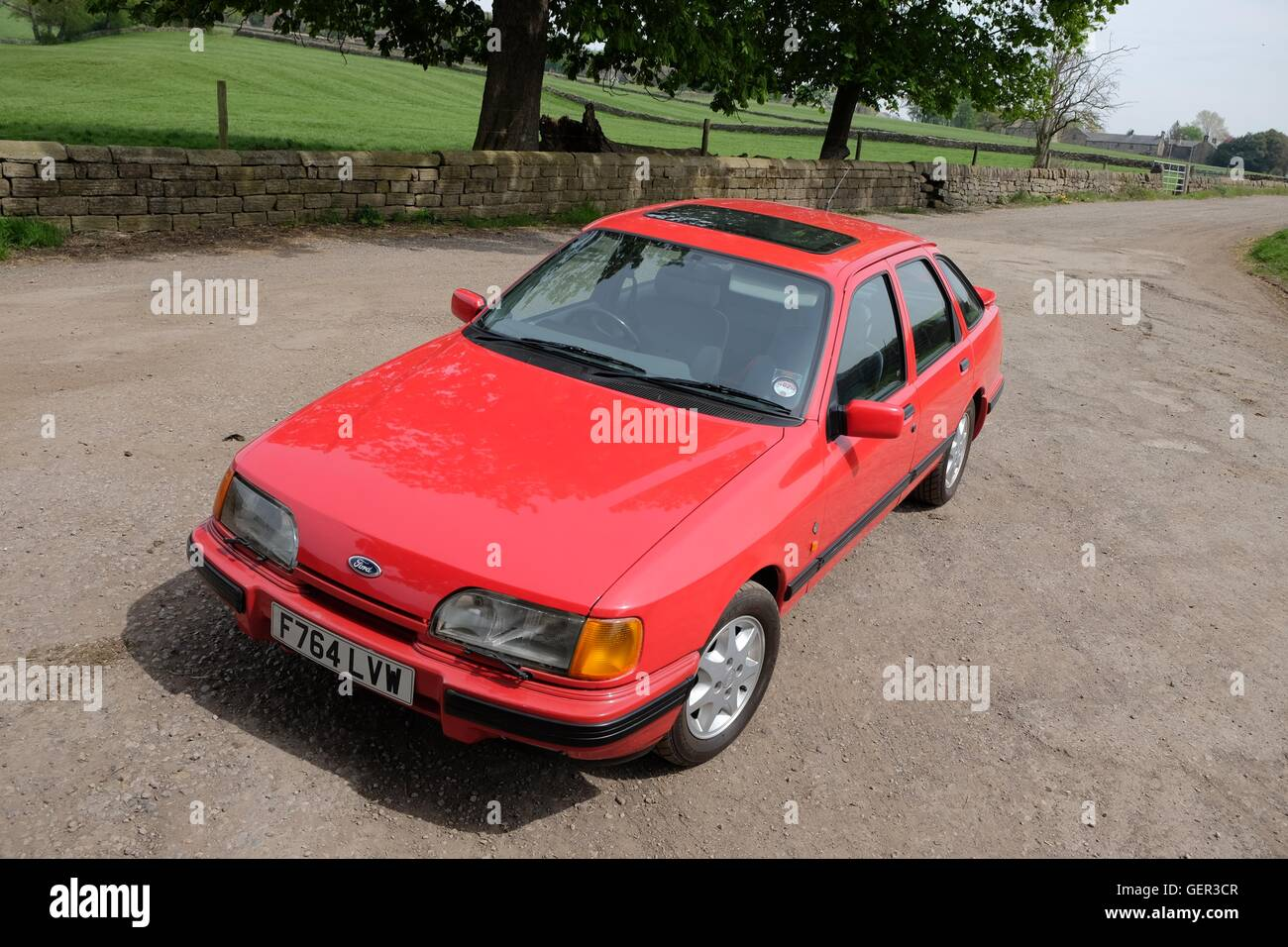 Ford Sierra XR 4x4 standing on a quiet country lane in Summer - Stock Image
